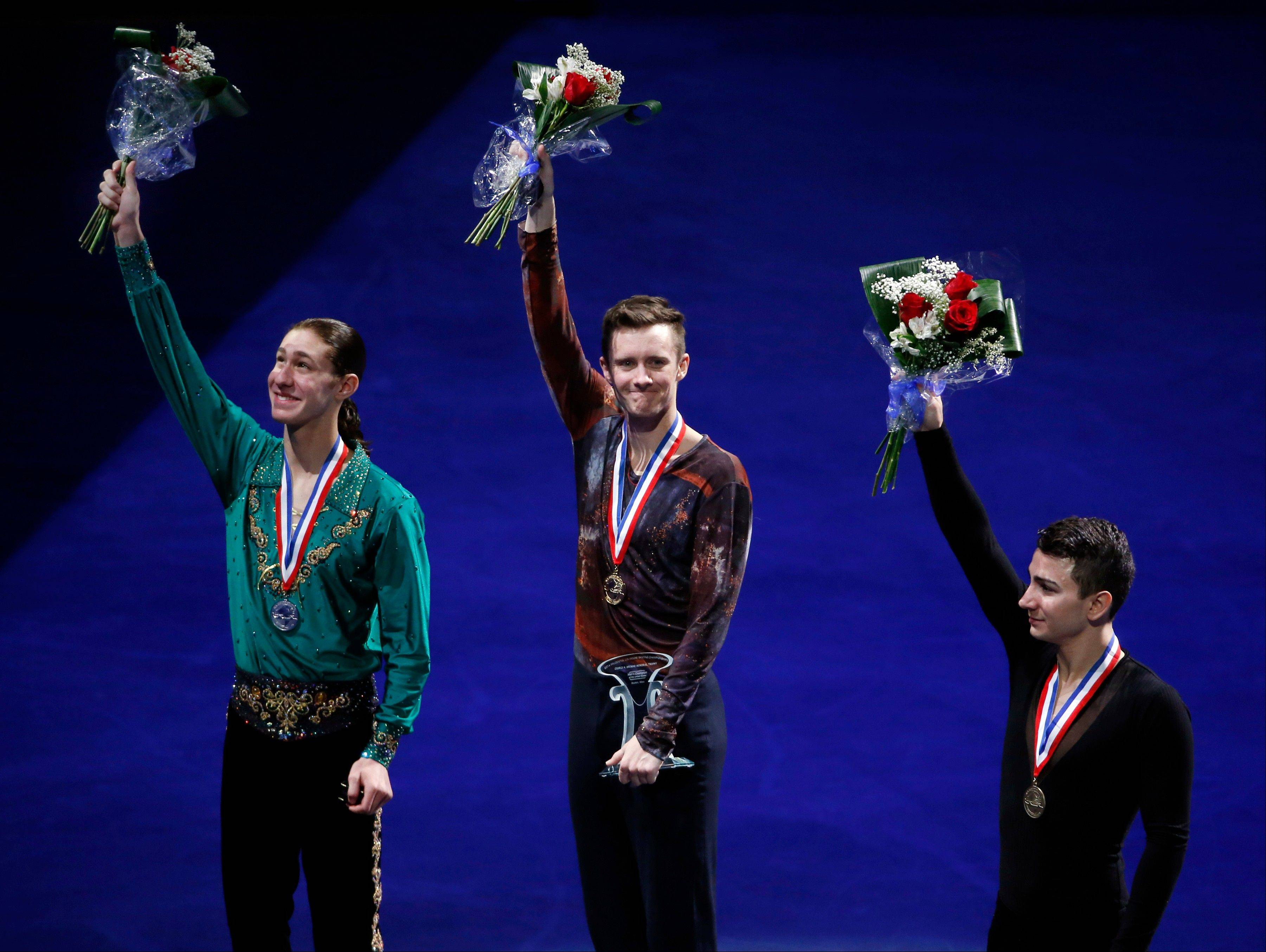 The top three men's skaters, from left, Jason Brown, Jeremy Abbott and Max Aaron, wave their flowers Sunday on the awards stand at the U.S. Figure Skating Championships in Boston.