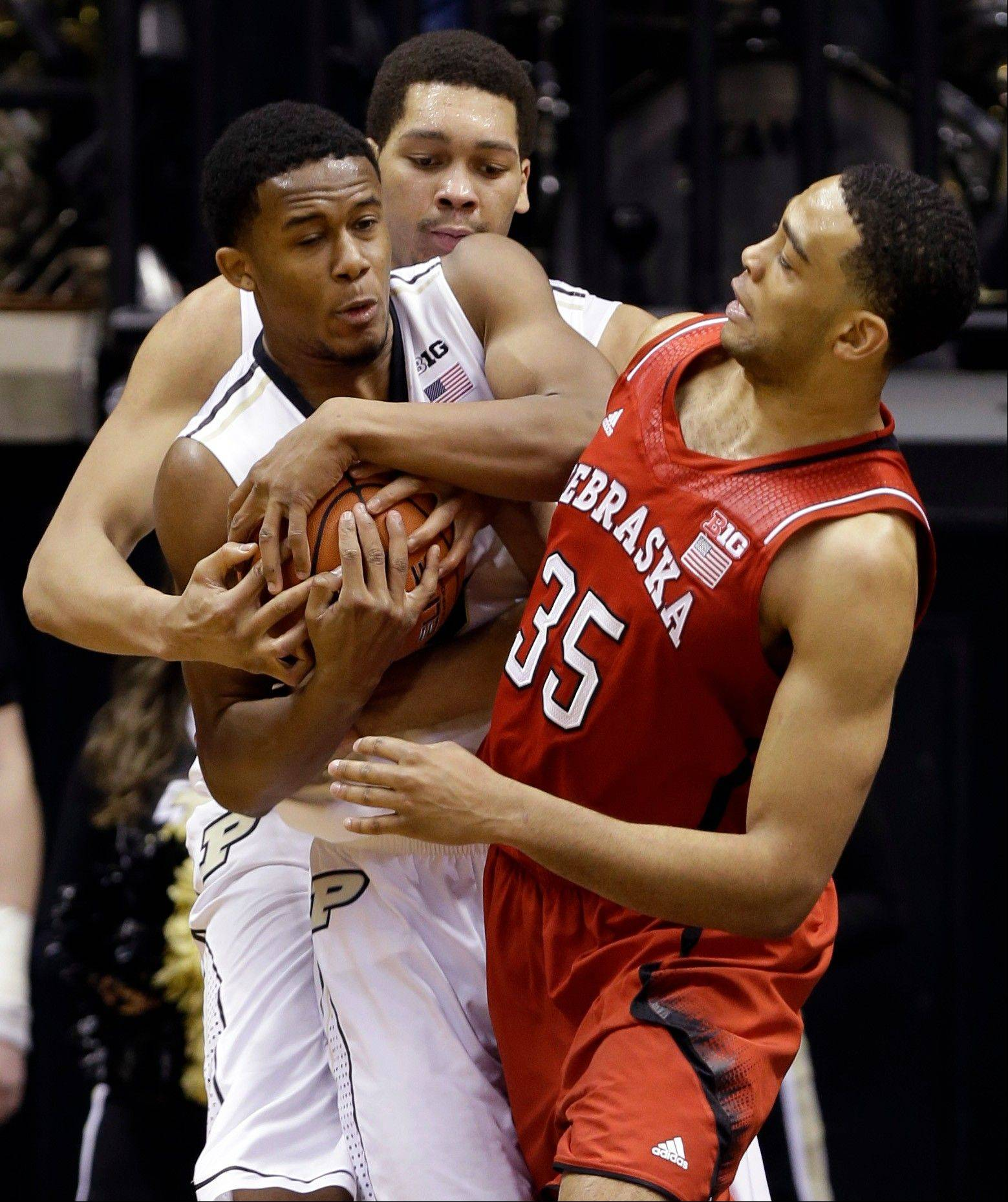 Nebraska forward Walter Pitchford, right, gets tied up with Purdue forward Basil Smotherman, left front, and center A.J. Hammons in the second half of Sunday's game in West Lafayette, Ind.