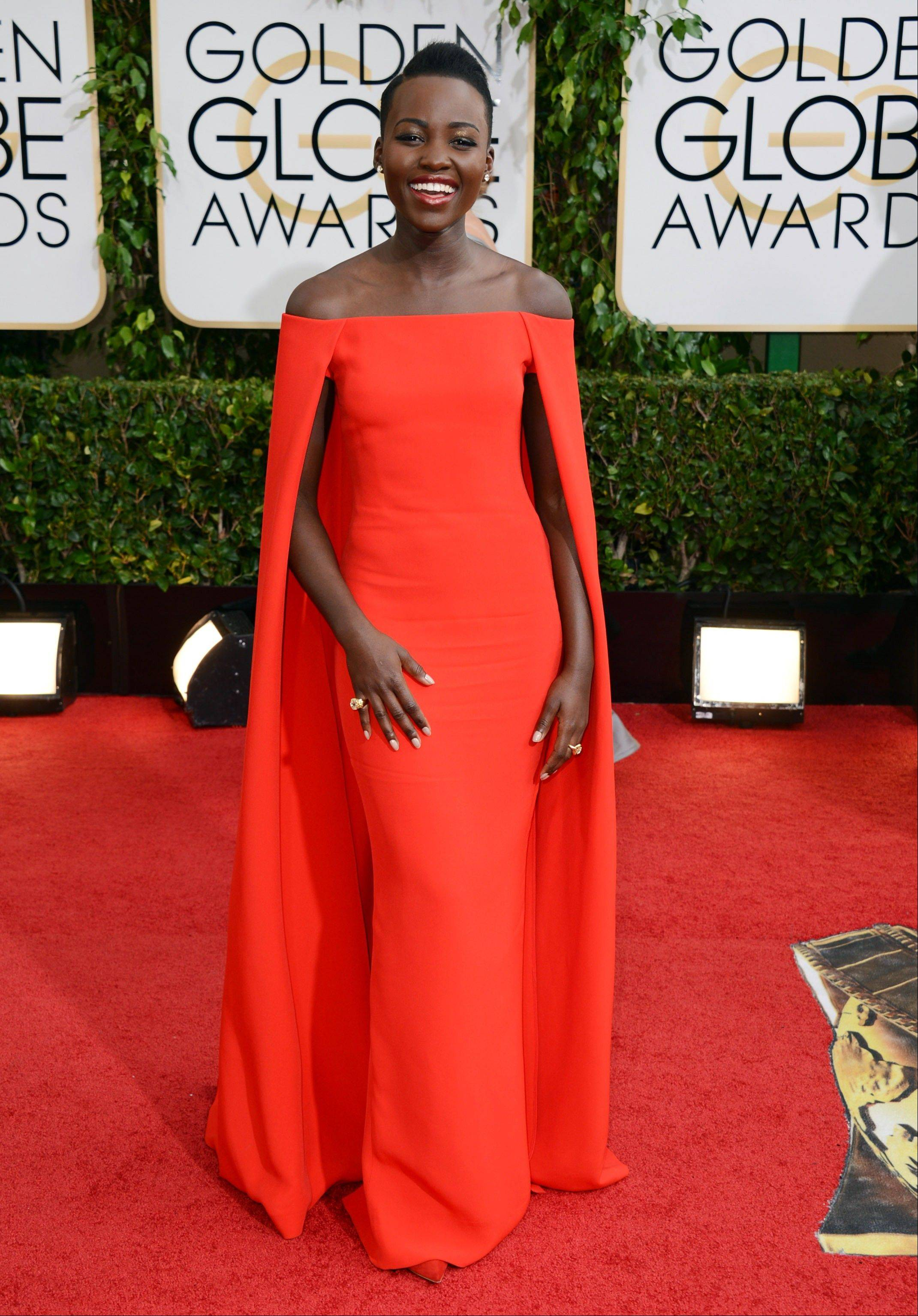 Newcomer Lupita Nyong'o stunned in an orange-red silk column gown with a cape from the Ralph Lauren Collection at the Golden Globes.