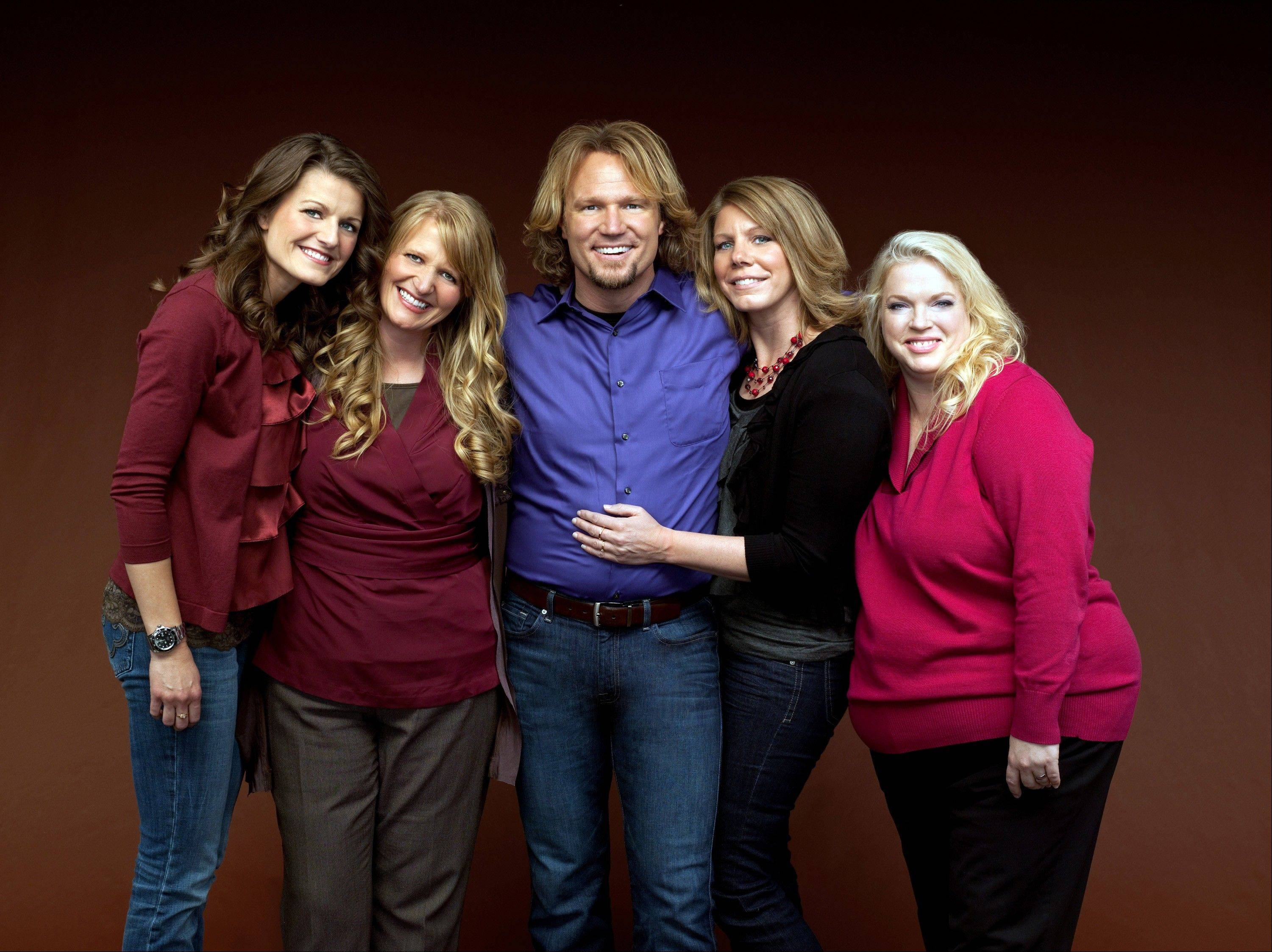 "Kody Brown, center, poses with his wives -- Robyn, left, Christine, Meri and Janelle -- for TLC's reality series ""Sister Wives."" When the polygamous family learned in December 2013 that a federal judge in Utah struck down key parts of the state's polygamy laws, Brown and his four wives said they cried and felt deeply emotional."