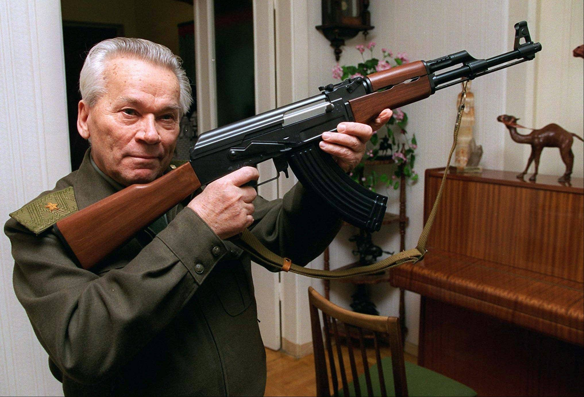 Mikhail Kalashnikov shows a model of his world-famous AK-47 assault rifle at his home in the Ural Mountain city of Izhevsk in October 1997.