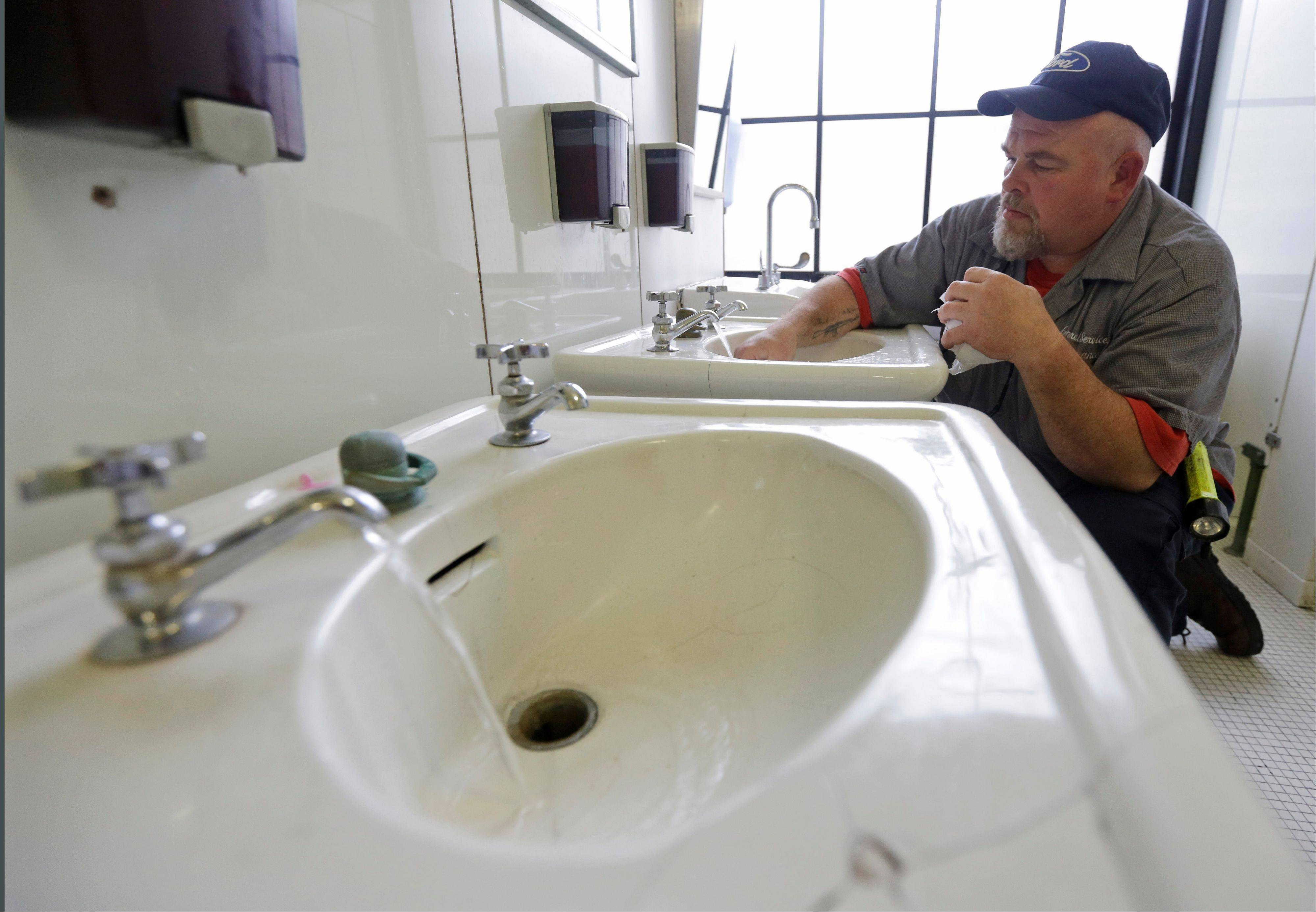 Al Jones of the West Virginia department of General Services flushes the water as he opens a rest room on the first floor of the State Capitol in Charleston, Va., Monday. Gov. Earl Tomblin announced that the water system is ready to be flushed by zones with safe drinking water after the chemical spill on Jan. 9.