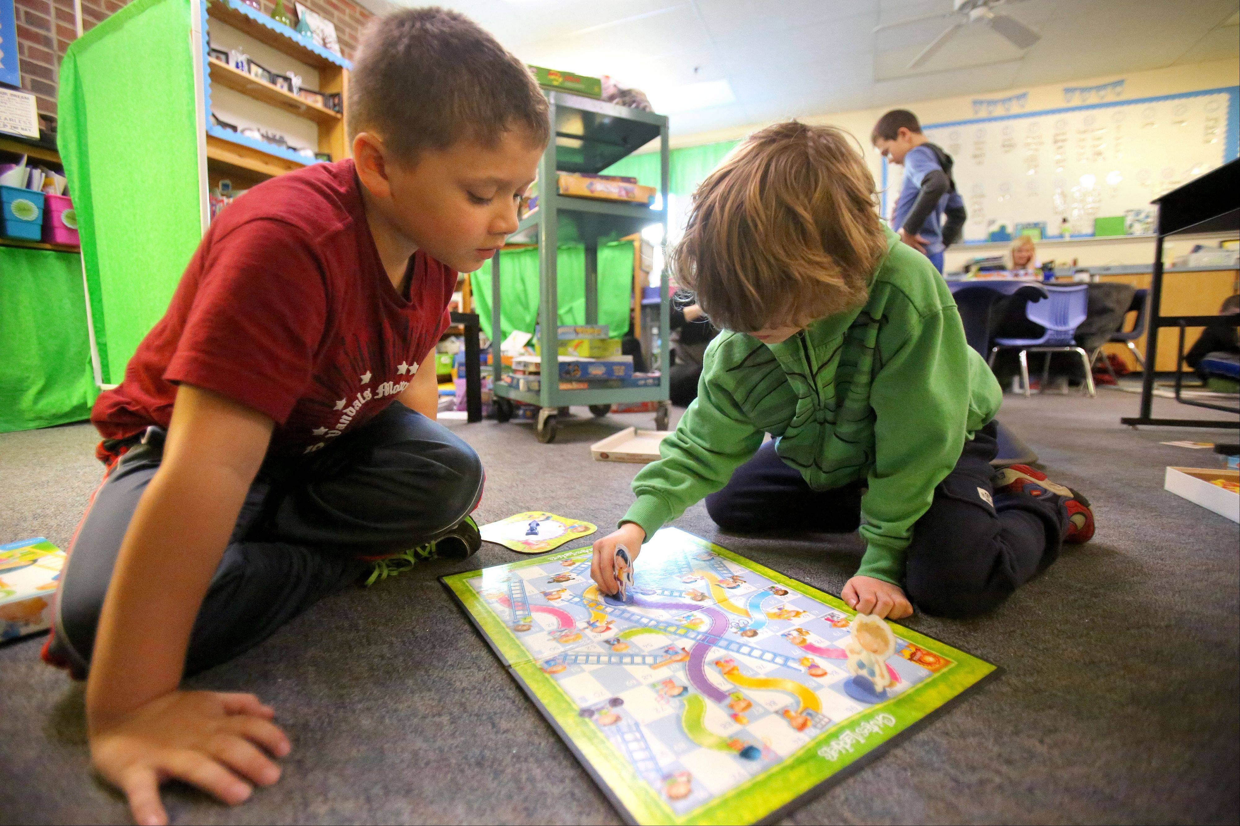 "Nathan Rojas, left, and Evan Dunbar, both 7 and from Libertyville, play a game of ""Chutes and Ladders"" on Monday during an after-school program called Games Galore at Rockland Elementary School in Libertyville."