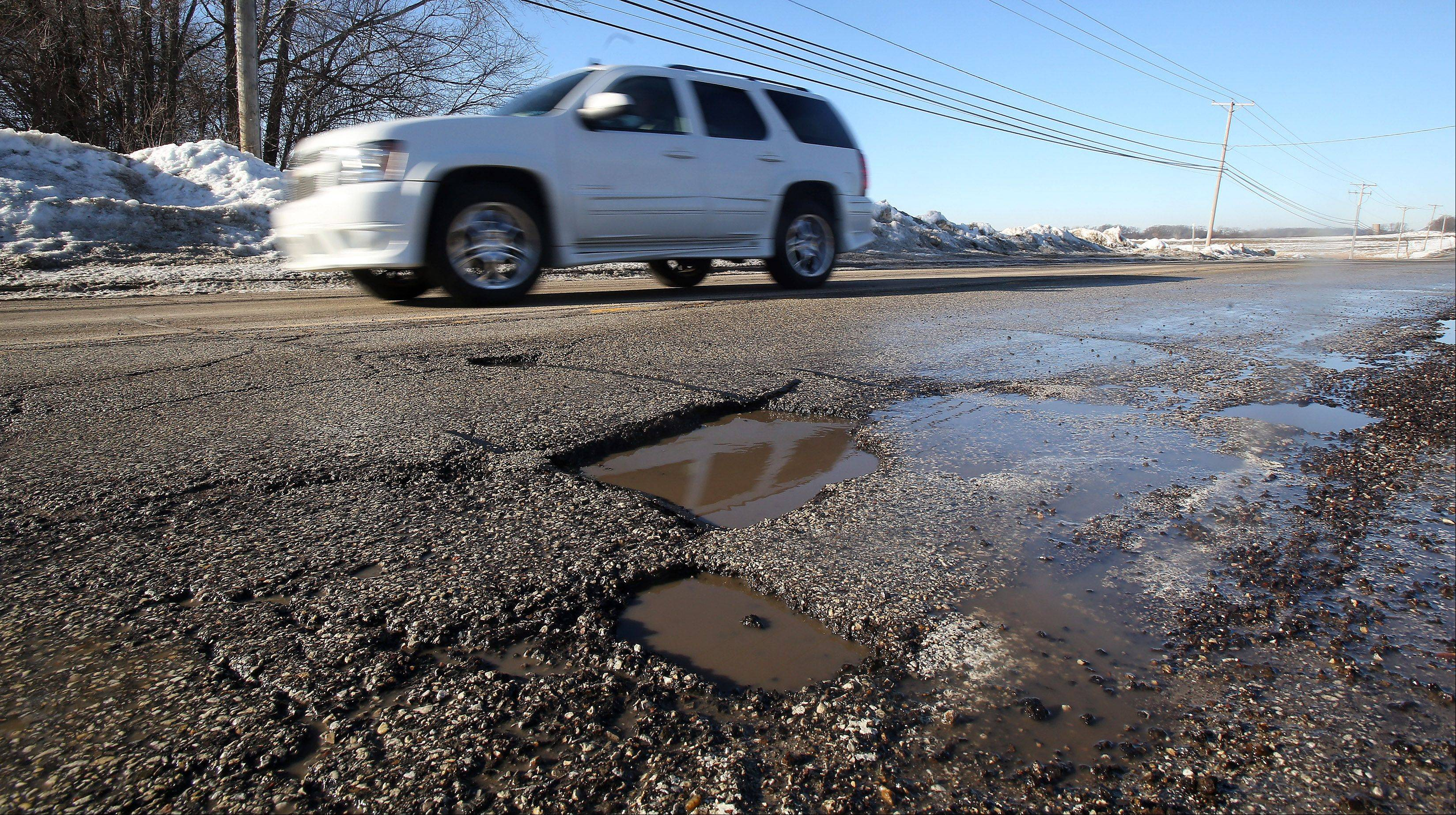A truck passes by a pothole on Alleghany Road in Hainesville on Monday. After heavy snow and frigid conditions, roadways are experiencing large numbers of potholes in Lake County.