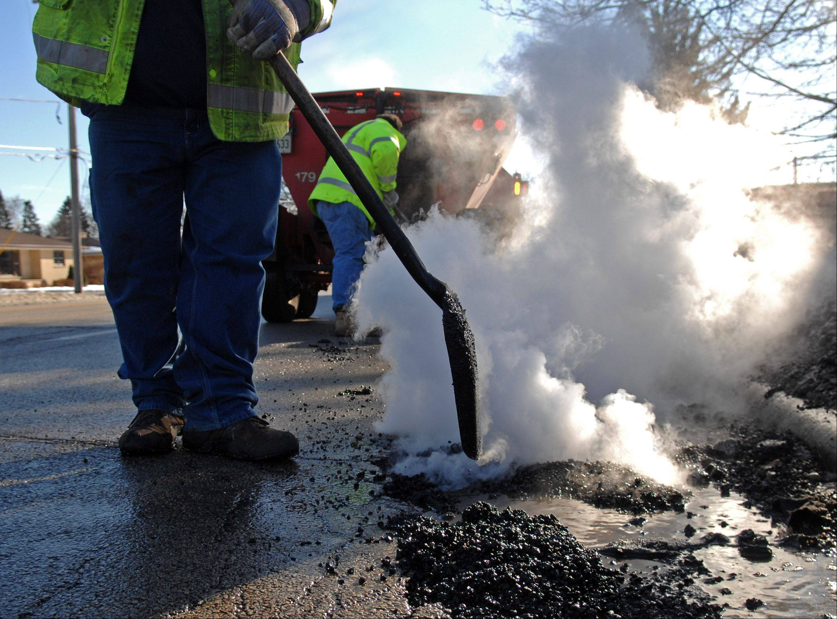 Workers from the Elgin public works department fix potholes along McLean Boulevard Monday afternoon.