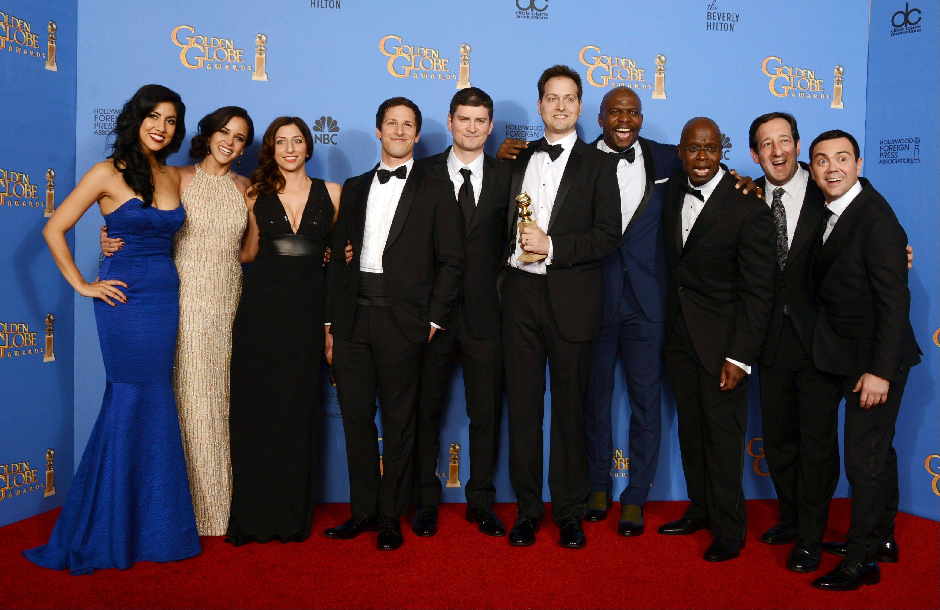 "From left, Stephanie Beatriz, Melissa Fumero, Chelsea Peretti, Andy Samberg, Michael Schur, Dan Goor, Terry Crews, Andre Braugher, David Miner and Joe Lo Truglio pose in the press room with the award for best television series -- comedy or musical for ""Brooklyn Nine -- Nine"" at the 71st annual Golden Globe Awards at the Beverly Hilton Hotel on Sunday, Jan. 12, 2014, in Beverly Hills, Calif."