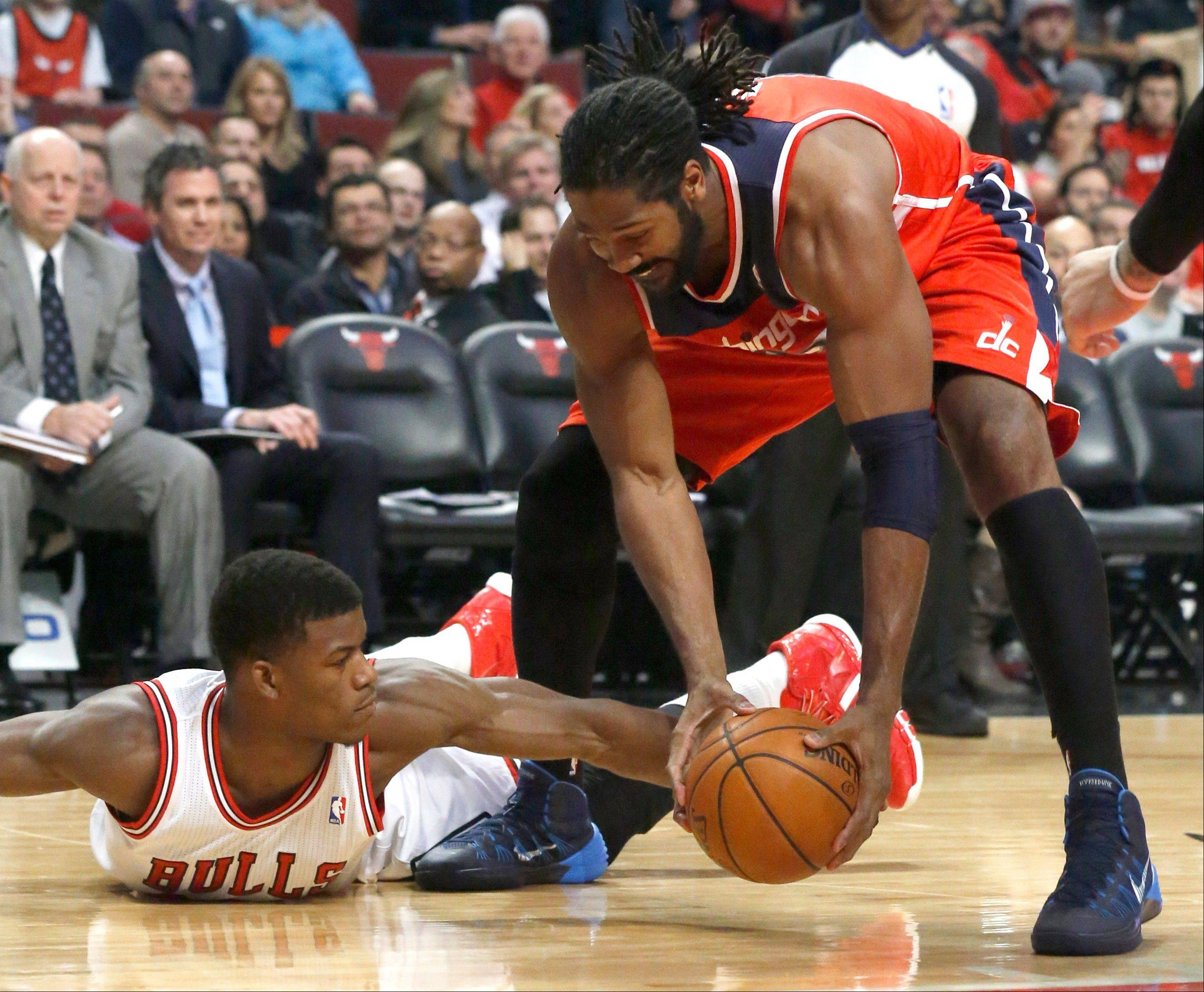 Bulls guard Jimmy Butler, left, battles Washington Wizards forward Nene during the first half of an NBA basketball game, Monday, Jan. 13, 2014, in Chicago.