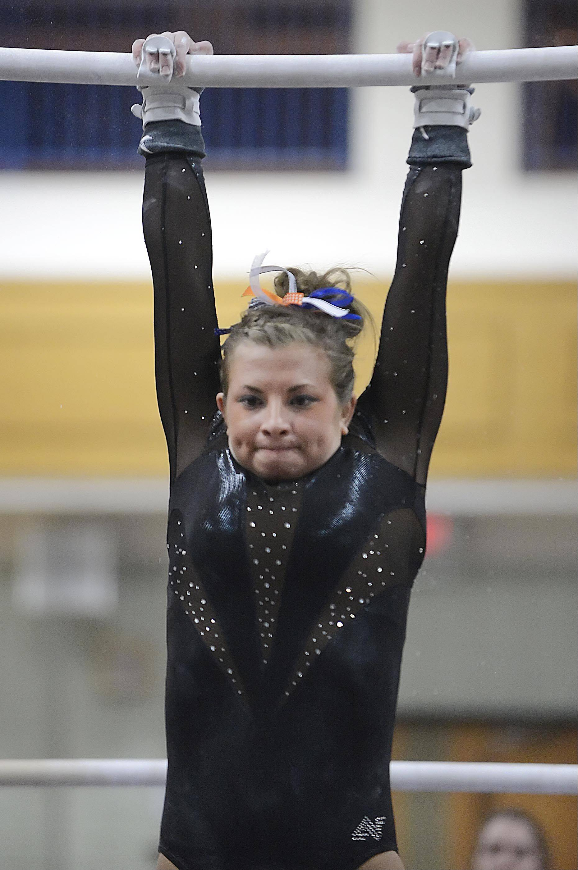St. Charles co-op's Kelly Gorniak competes against Geneva in the uneven parallel bars Monday in Geneva.