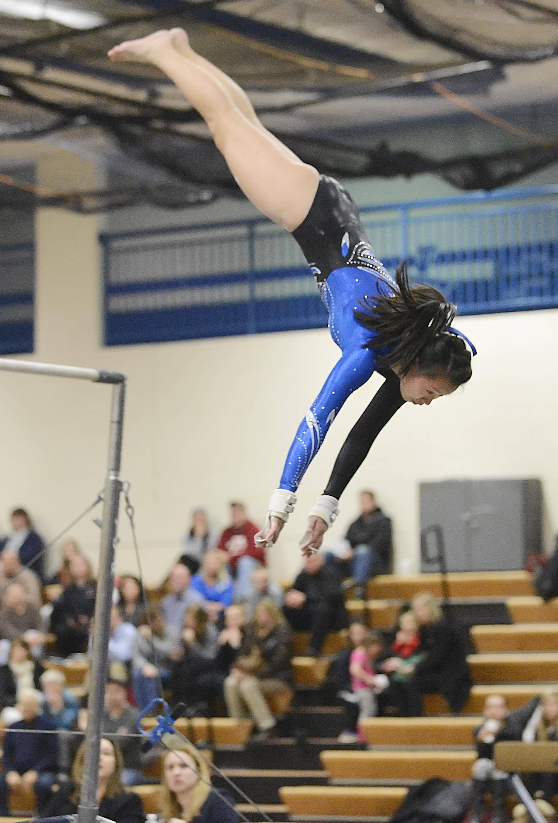 Geneva's Claire Scatterday dismounts the uneven parallel bars Monday against St. Charles co-op in Geneva. Scatterday was one of two seniors honored Monday.