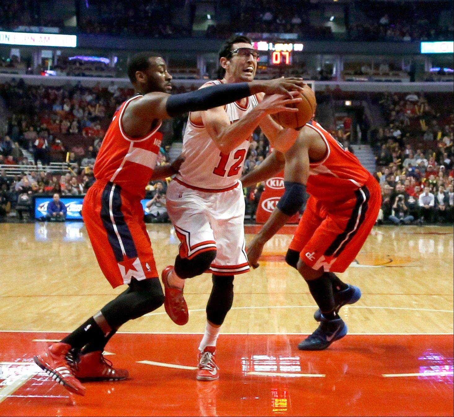 Bulls guard Kirk Hinrich drives between Washington Wizards guard John Wall, left, and Nene, right, during the first half of an NBA basketball game Monday, Jan. 13, 2014, in Chicago.
