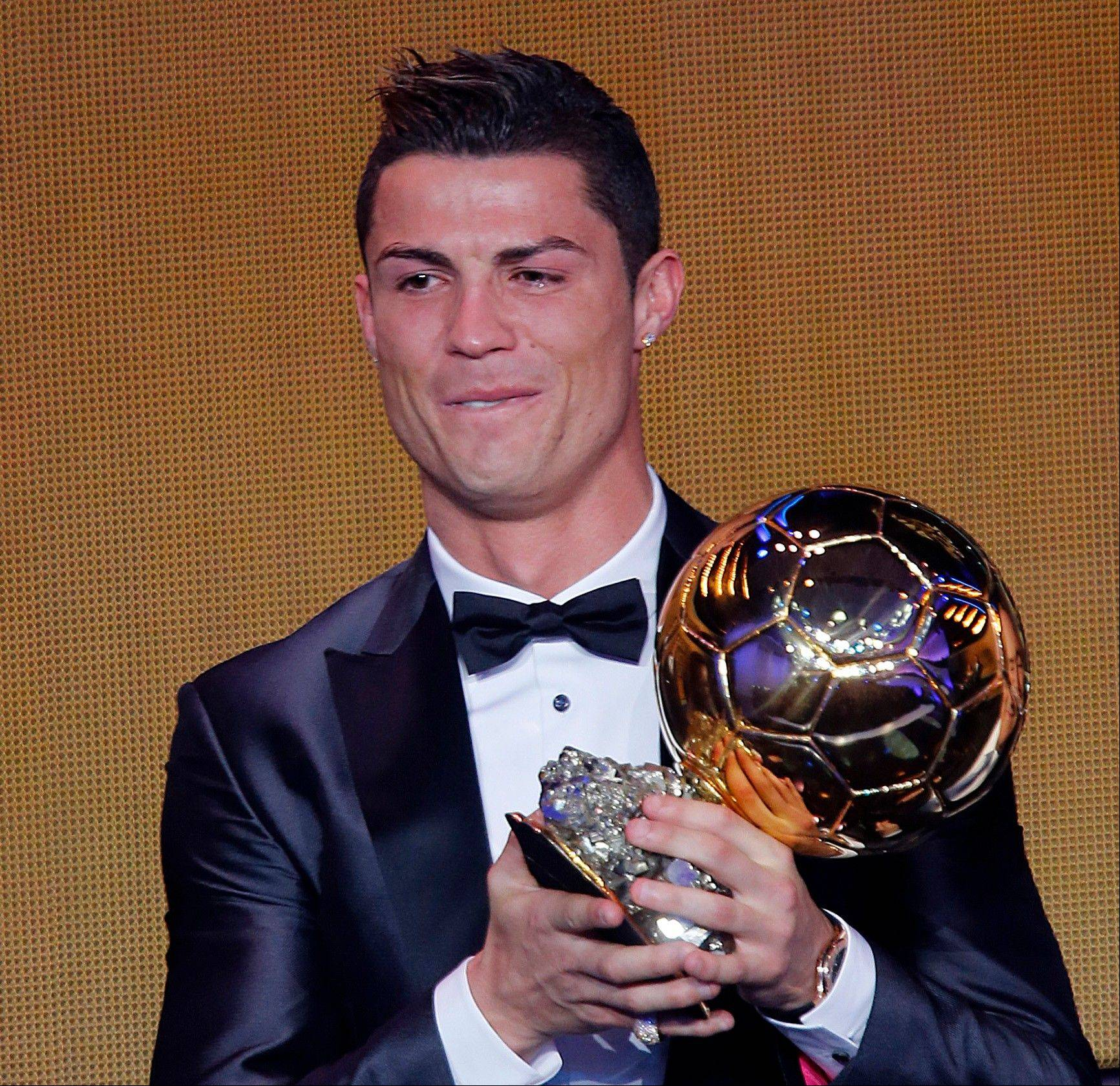 Real Madrid's Cristiano Ronaldo of Portugal cries as he holds the trophy for world player of the year at the FIFA Ballon d'Or 2013 Gala in Zurich, Switzerland, Monday, Jan. 13, 2014.