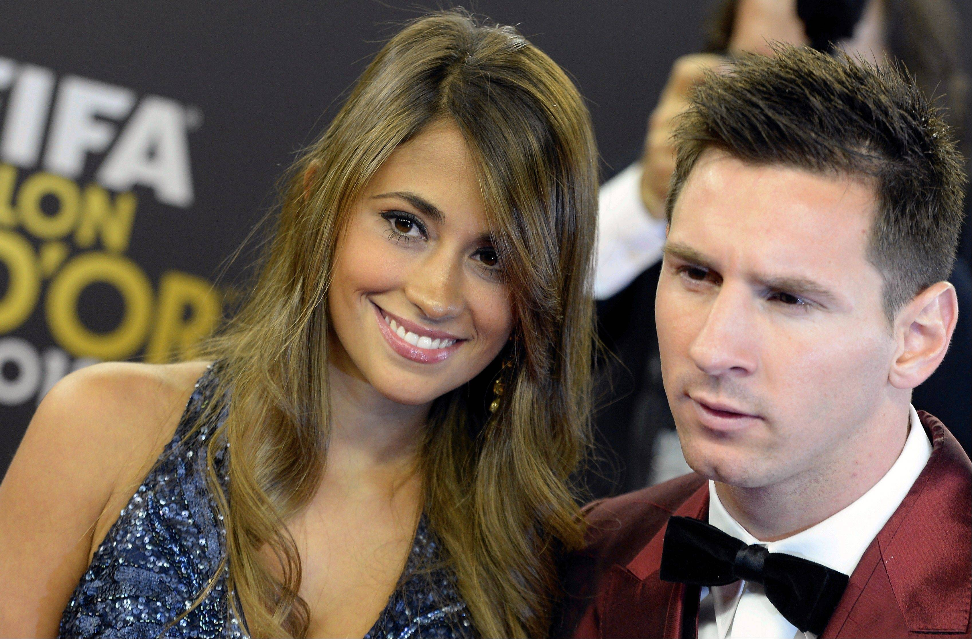 Soccer player Lionel Messi, right, of Argentina arrives with his wife Antonella, left, on the red carpet prior to the FIFA Ballon d'Or 2013 gala held at the Kongresshaus in Zurich, Switzerland, Monday, Jan. 13, 2014.