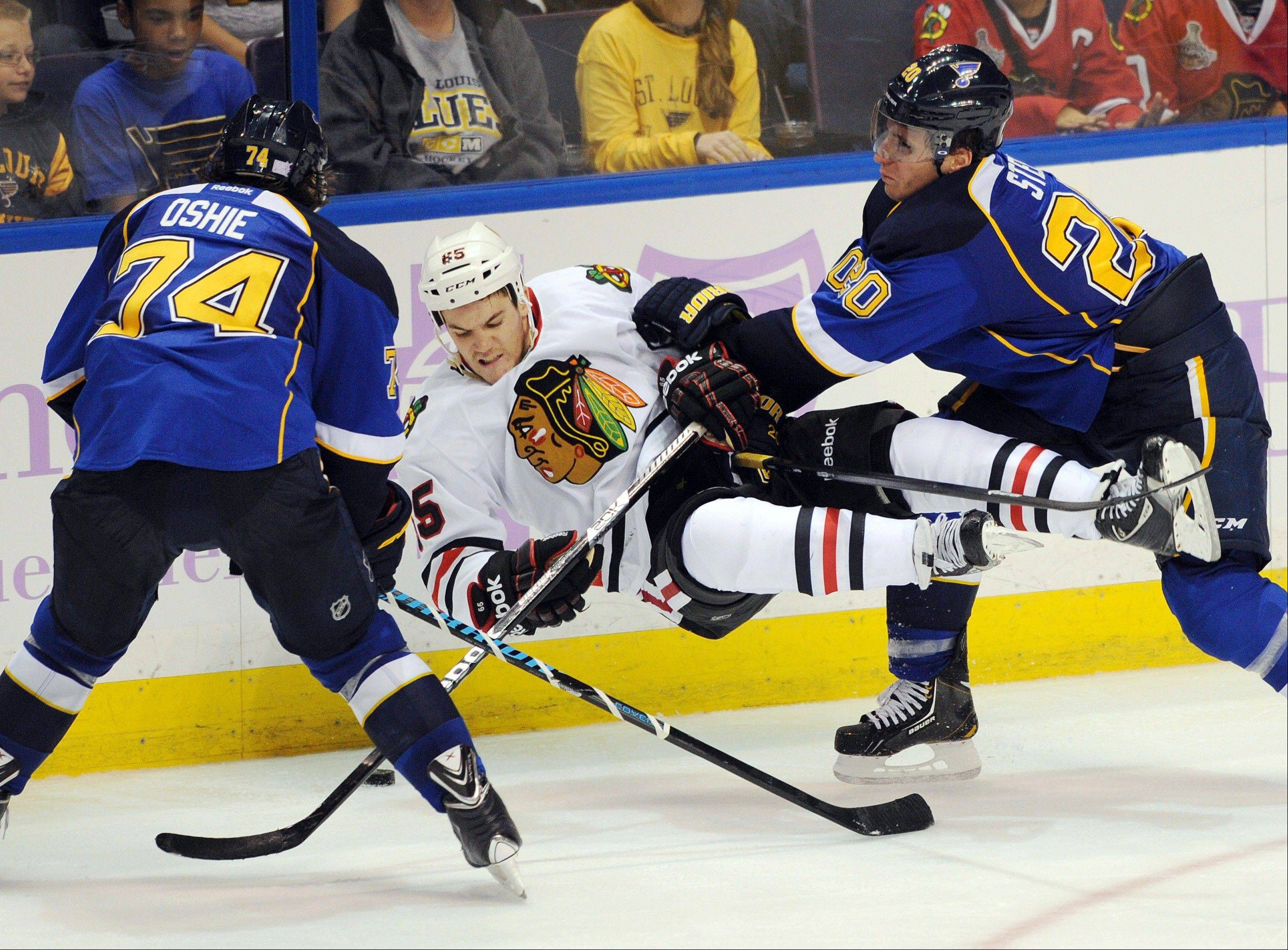 The St. Louis Blues' Alexander Steen, right, checks the Blackhawks' Andrew Shaw, center, as Blues' T.J. Oshie watches during the third period of an NHL hockey game Wednesday, Oct. 9, 2013, in St. Louis.