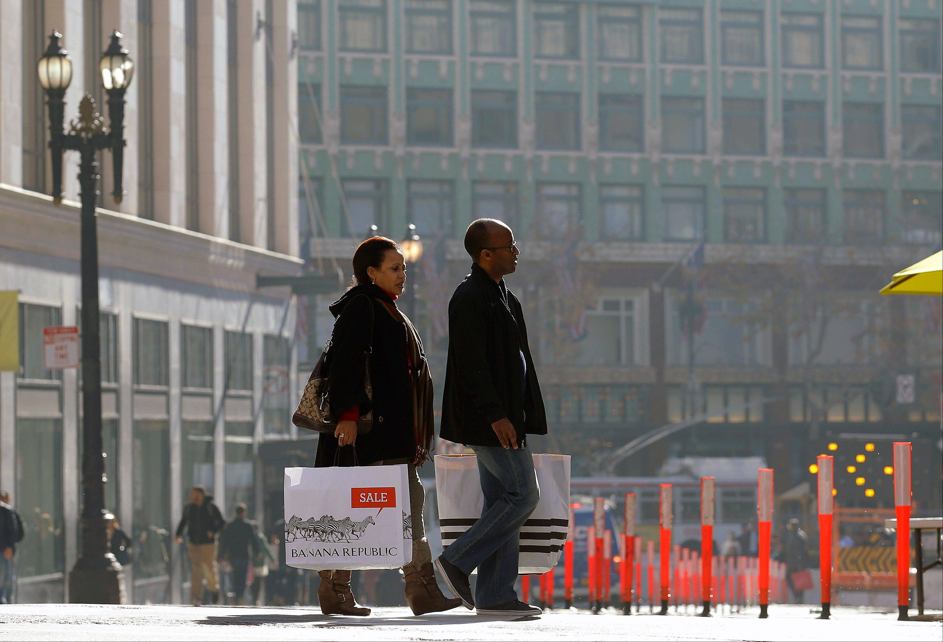 A man and woman carry shopping bags as they cross the street in San Francisco. Americans bought more clothing in December, clicked frequently at online retailers and paid higher gas prices.