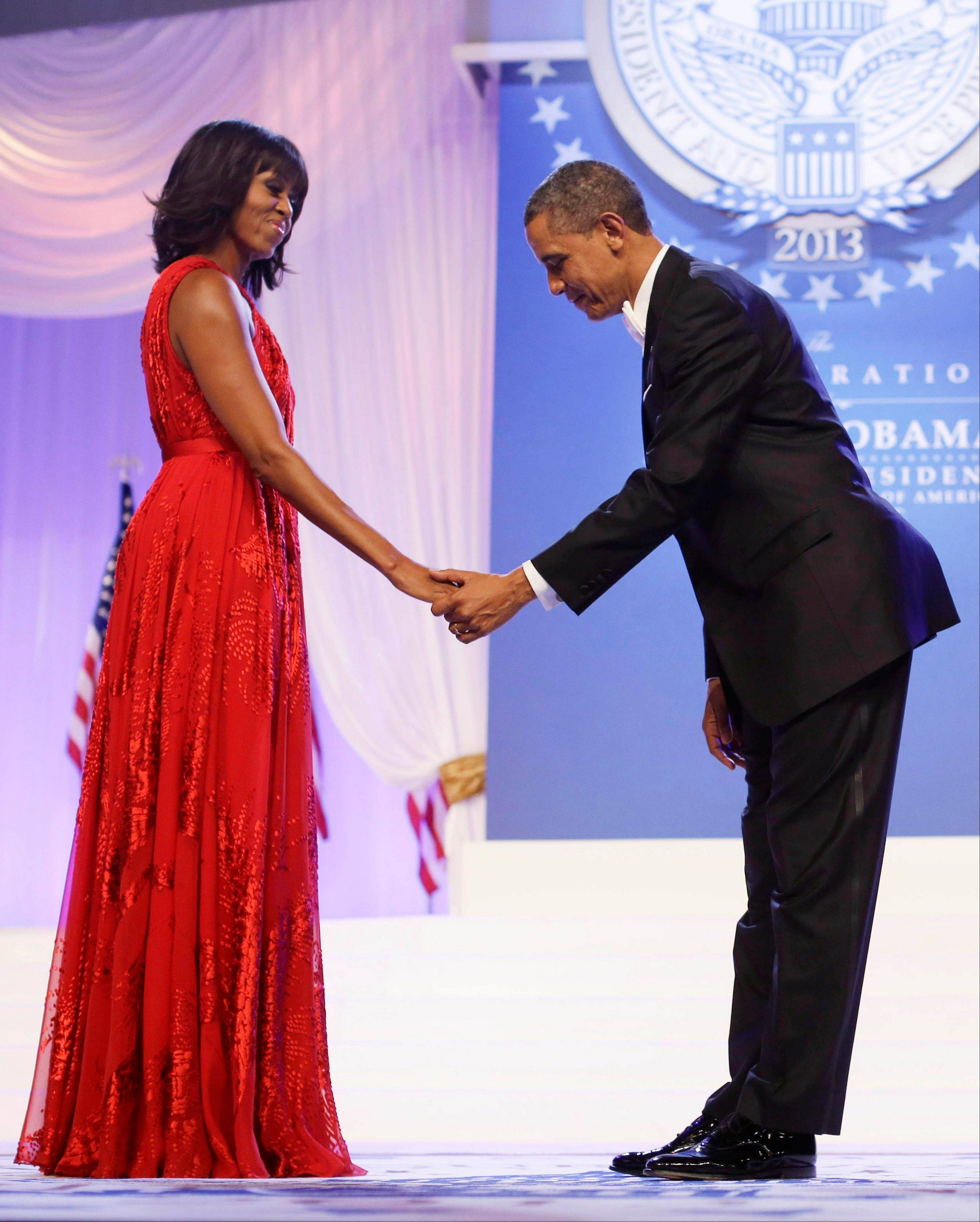 President Barack Obama bows as he and first lady Michelle Obama, wearing a ruby-colored chiffon and velvet Jason Wu gown, gets ready to dance at the Inaugural Ball at the Washington Convention Center during the 57th Presidential Inauguration in Washington. Michelle Obama�s fashion is making history again, at least for the next year, as her second inaugural gown will be displayed at the Smithsonian Institution.
