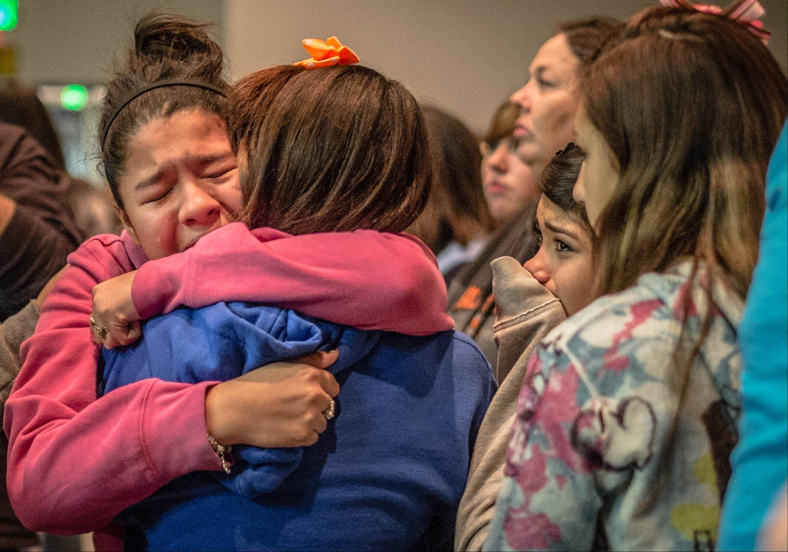 Thirteen-year-old Kimberly Macias cries as she sees schoolmates at a vigil for the victims Tuesday in Roswell, N.M.