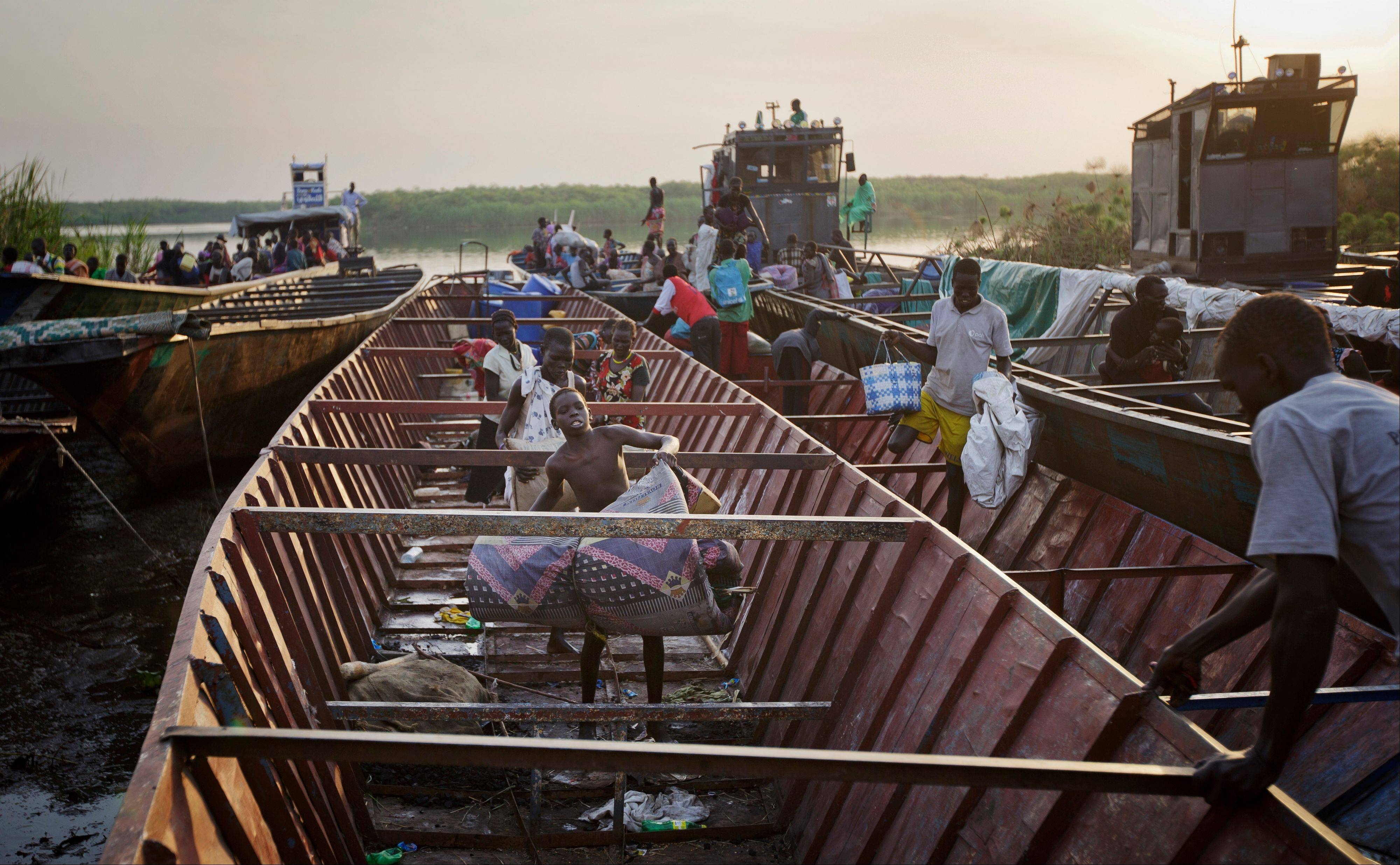 Displaced people arrive by river barge from Bor, some of the thousands who fled the recent fighting between government and rebel forces in Bor by boat across the White Nile. A military spokesman in South Sudan said that 200 people fleeing warfare elsewhere in the country died after a boat that was carrying mostly women and children sank while crossing the Nile River in Upper Nile State.