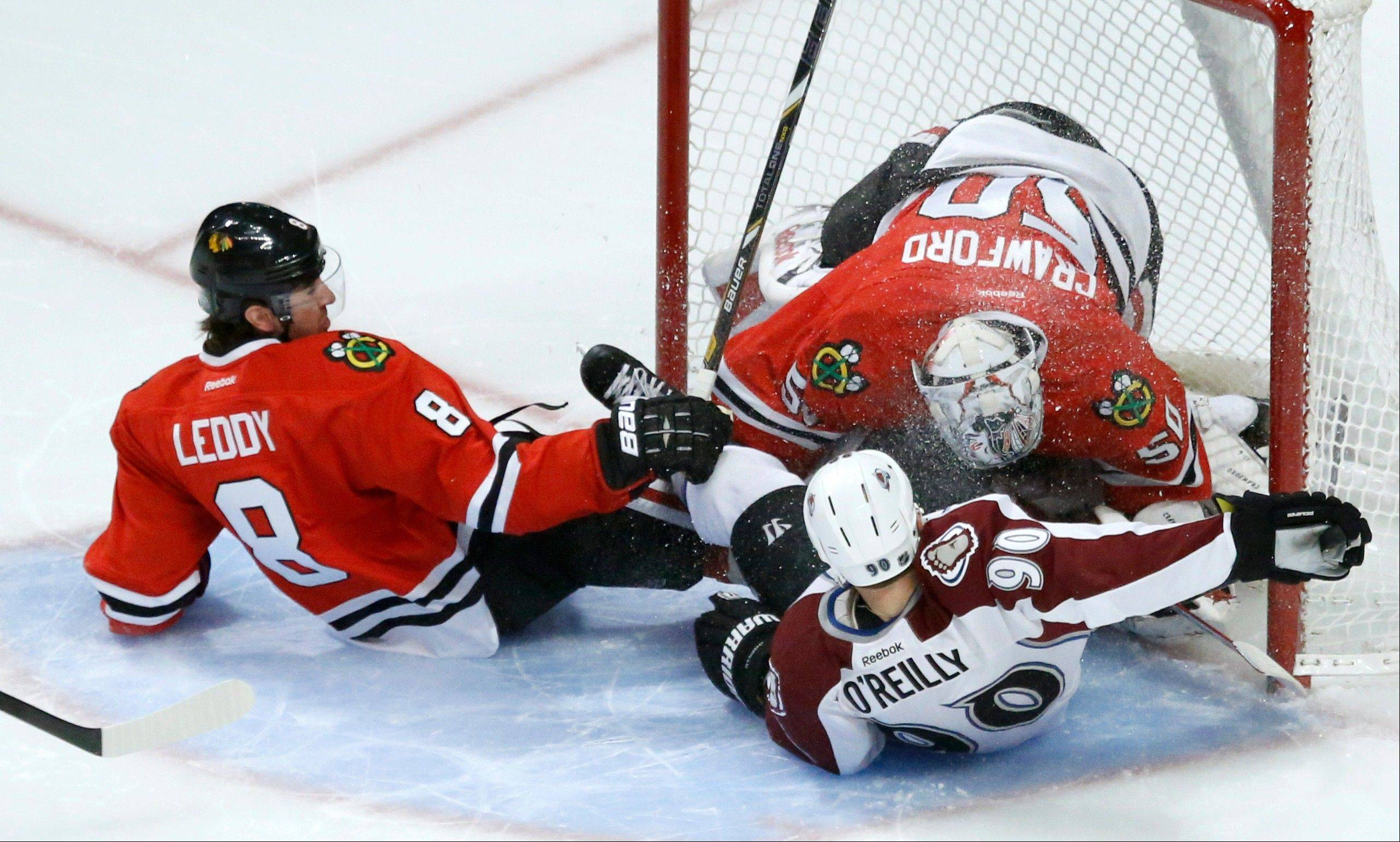 The Blackhawks� Nick Leddy (8) and Ryan O�Reilly of the Avalanche crash into goalie Corey Crawford during the first period Tuesday at the United Center.