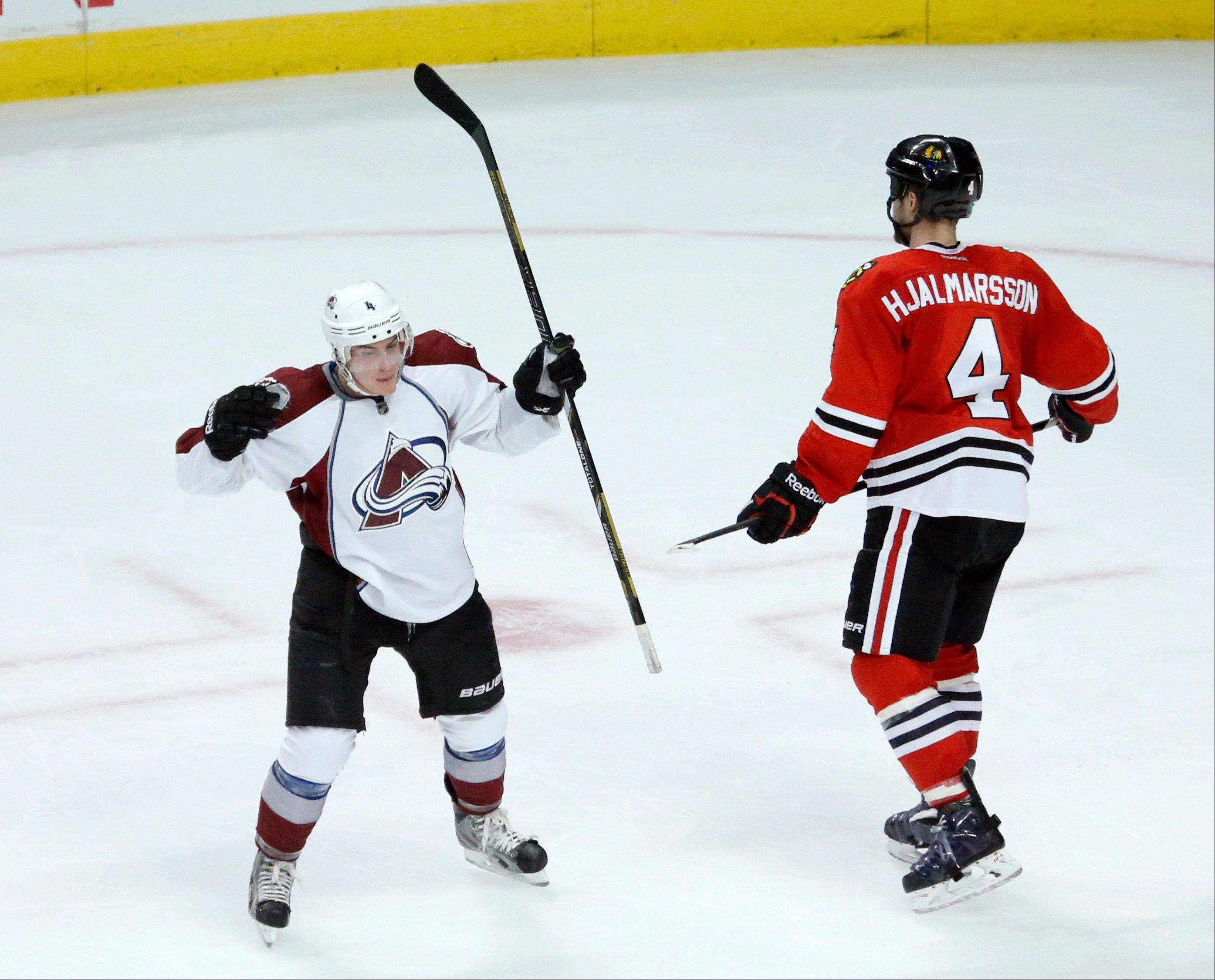 Colorado Avalanche defenseman Tyson Barrie (4) celebrates his winning goal in overtime as Chicago Blackhawks defenseman Niklas Hjalmarsson skates away in an NHL hockey game, Tuesday, Jan. 14, 2014, in Chicago. (AP Photo/Charles Rex Arbogast)