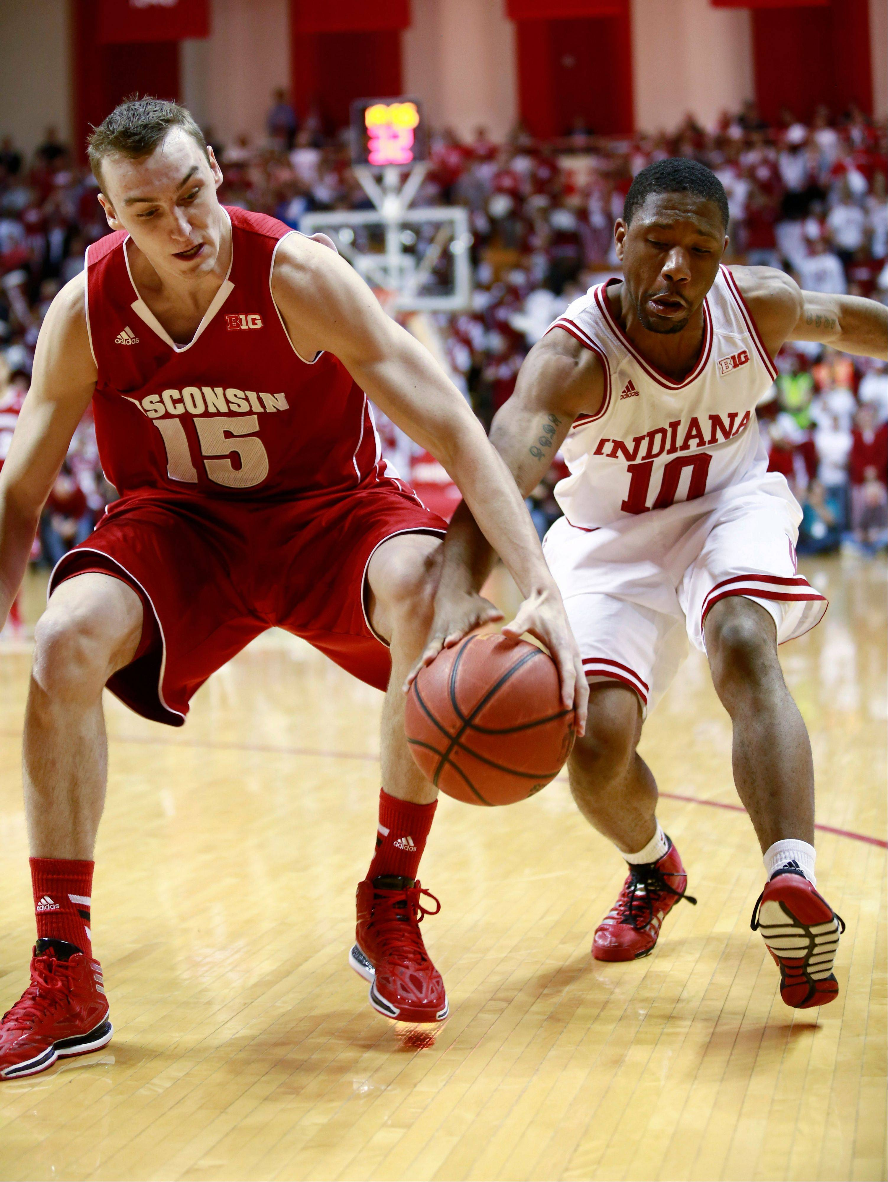 Wisconsin forward Sam Dekker (15) and Indiana guard Evan Gordon (10) fight for control of the basketball in the first half of an NCAA basketball game in Bloomington, Ind. Tuesday, Jan. 14, 2014. (AP Photo/R Brent Smith)