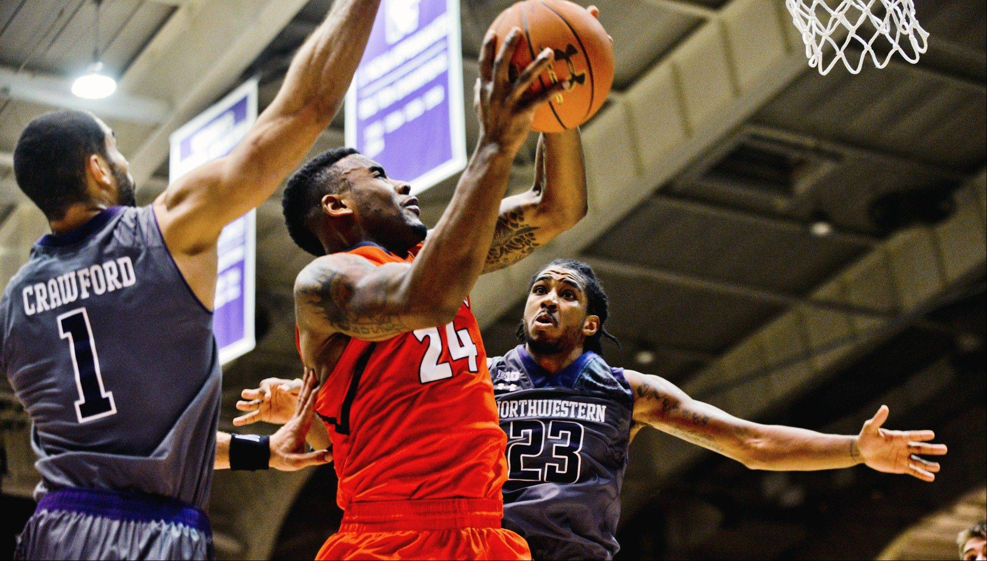 Illinois guard Rayvonte Rice (24) shoots between Northwestern's Drew Crawford (1) and guard JerShon Cobb (23) during the second half of an NCAA college basketball game in Evanston, Ill., on Sunday, Jan. 12, 2014. Northwestern won 49-43. (AP Photo/Matt Marton)