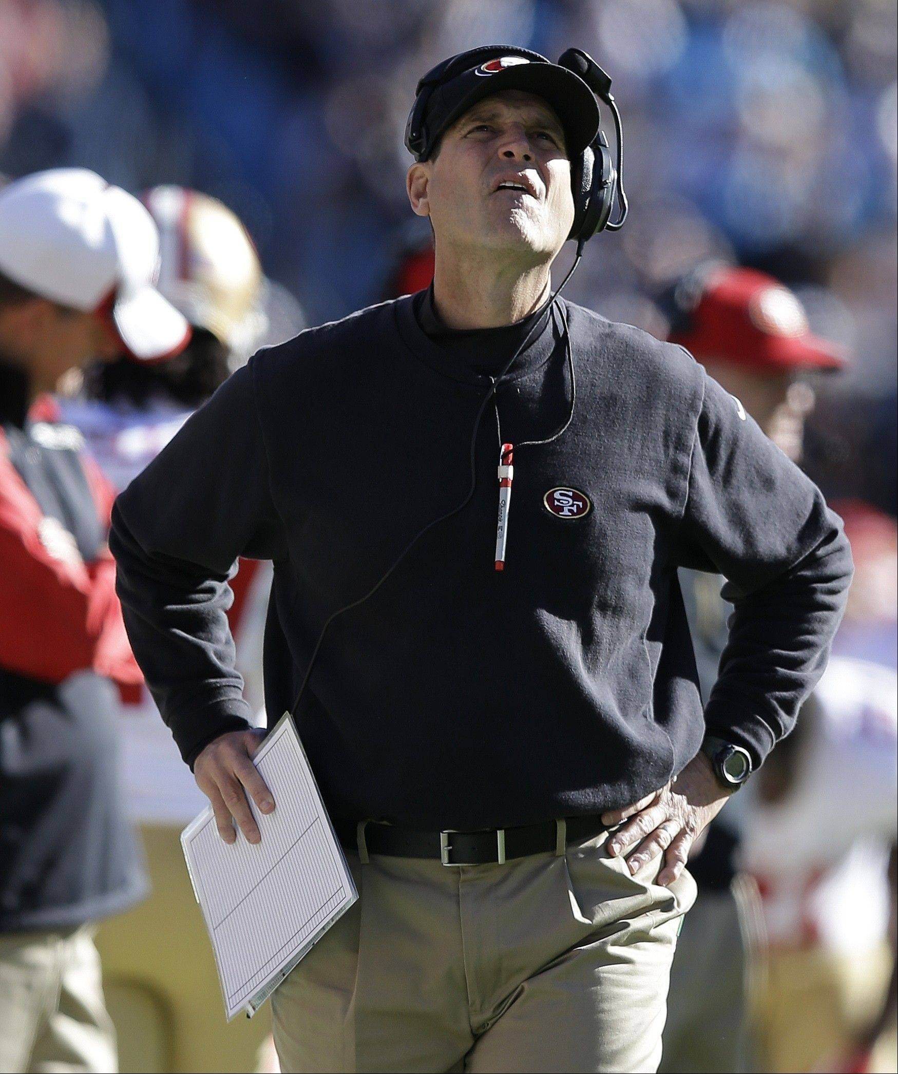 San Francisco 49ers head coach Jim Harbaugh watches the scoreboard against the Carolina Panthersduring the first half of a divisional playoff NFL football game, Sunday, Jan. 12, 2014, in Charlotte, N.C. (AP Photo/Gerry Broome)
