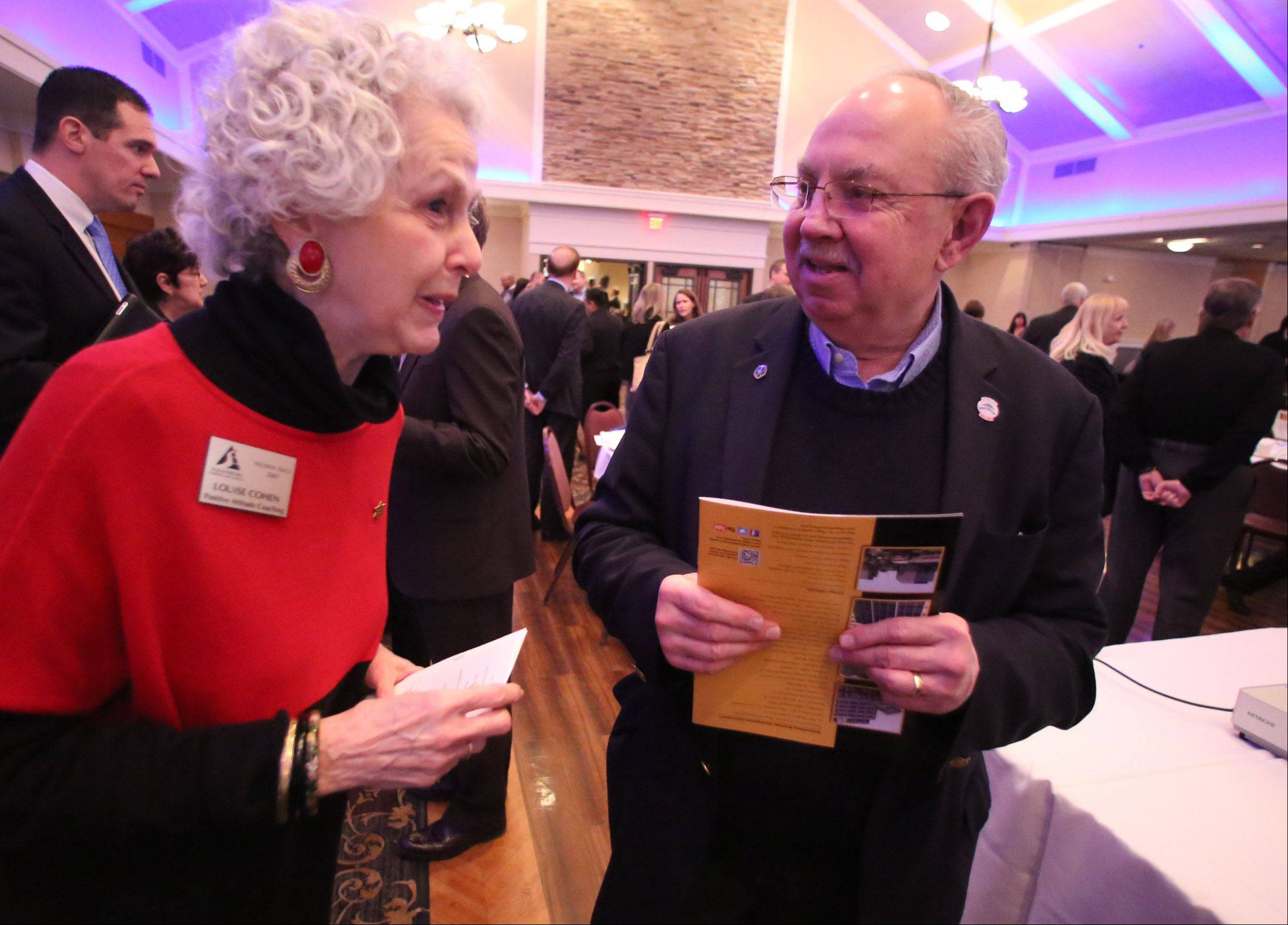 Schaumburg Mayor Al Larson speaks with Louise Cohen, owner of The Positive Attitude Coaching Program, after he delivered his annual state-of-the-village address and preview of the year ahead at the Schaumburg Business Association's monthly breakfast meeting Tuesday.
