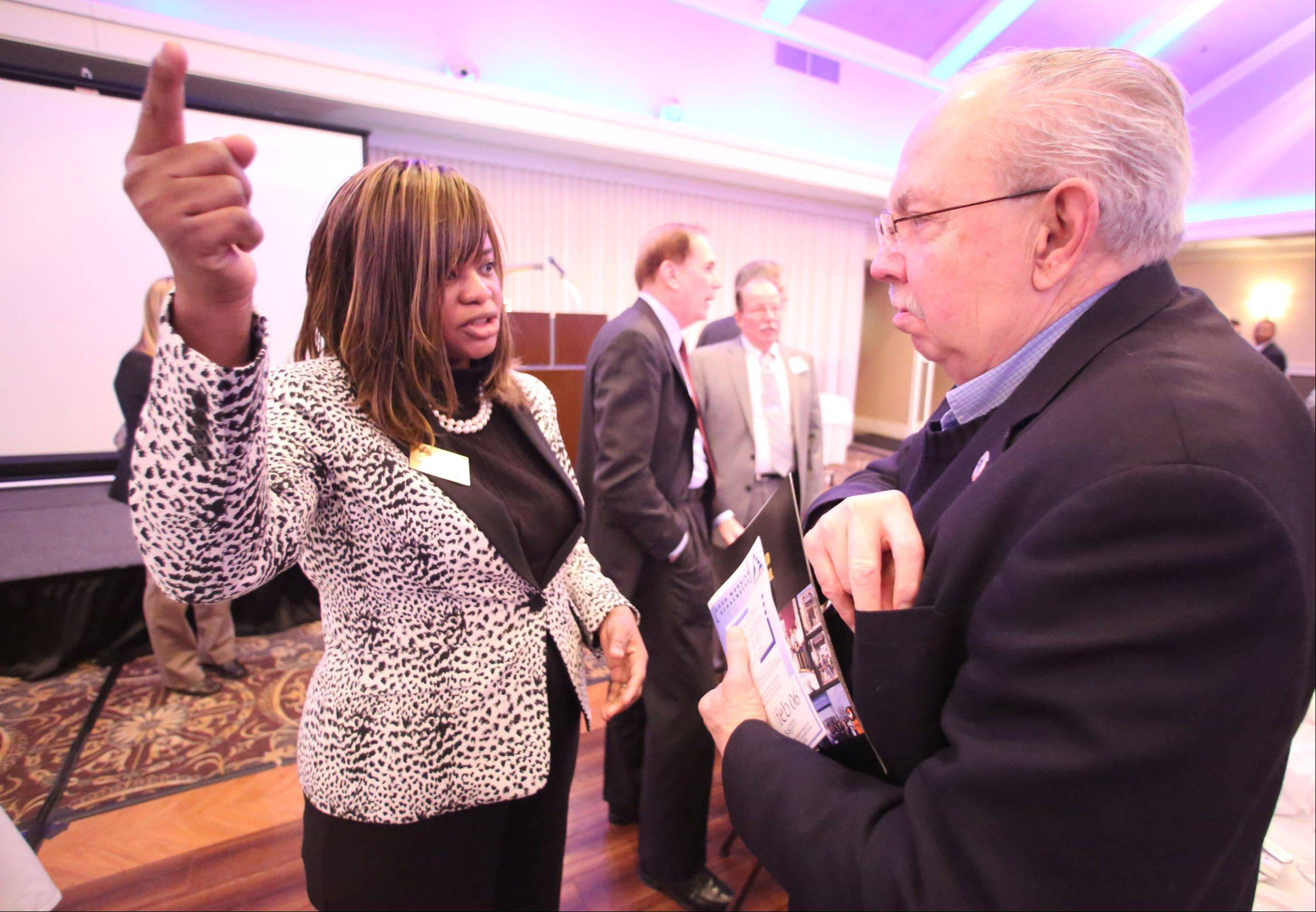 Schaumburg Mayor Al Larson speaks with Ris Orhorha, president of Center for Health Services, after he delivered his annual state-of-the-village address and preview of the year ahead at the Schaumburg Business Association's monthly breakfast meeting Tuesday.