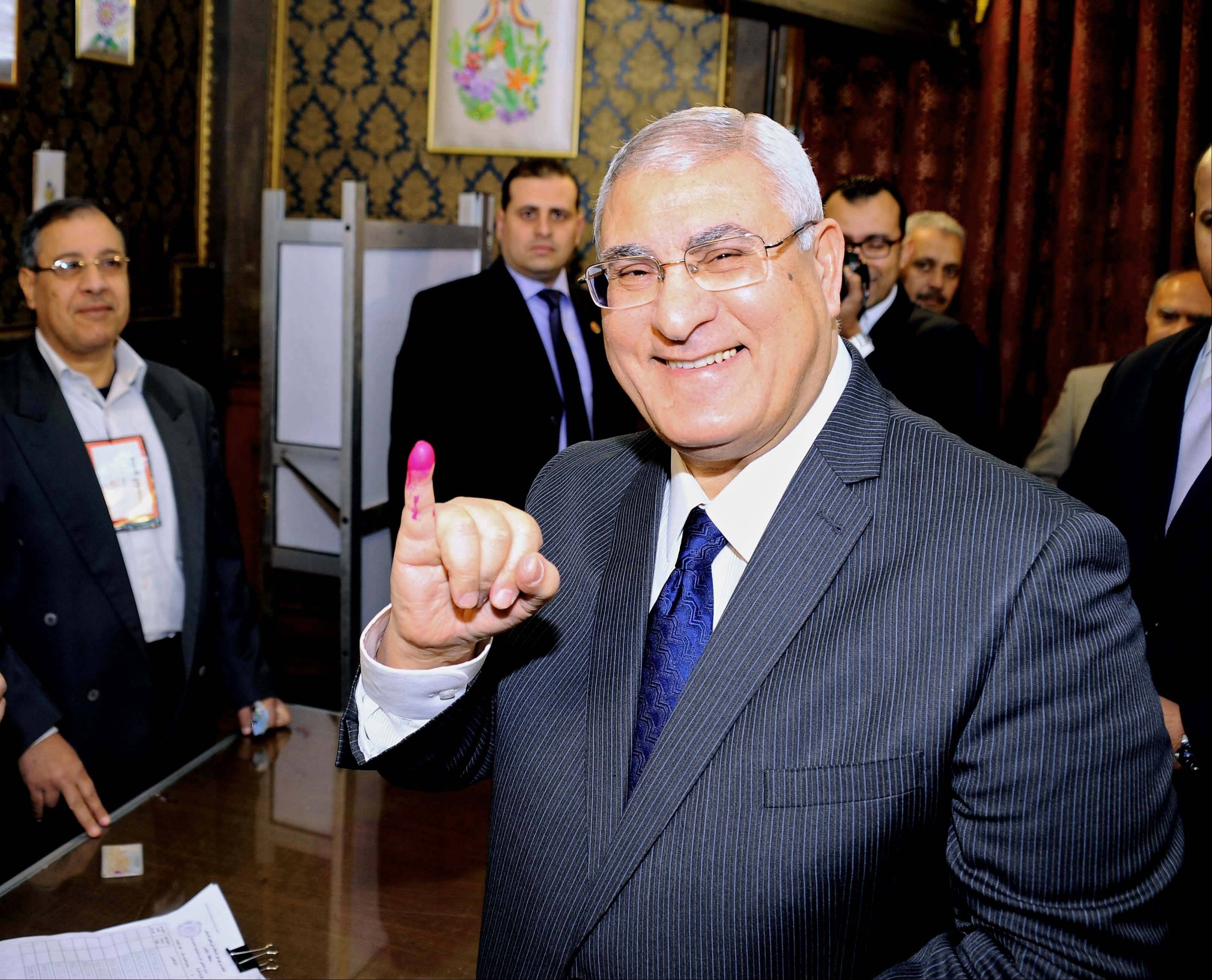 Interim President Adly Mansour shows his ink-stained finger after casting his vote at a polling station in Cairo.