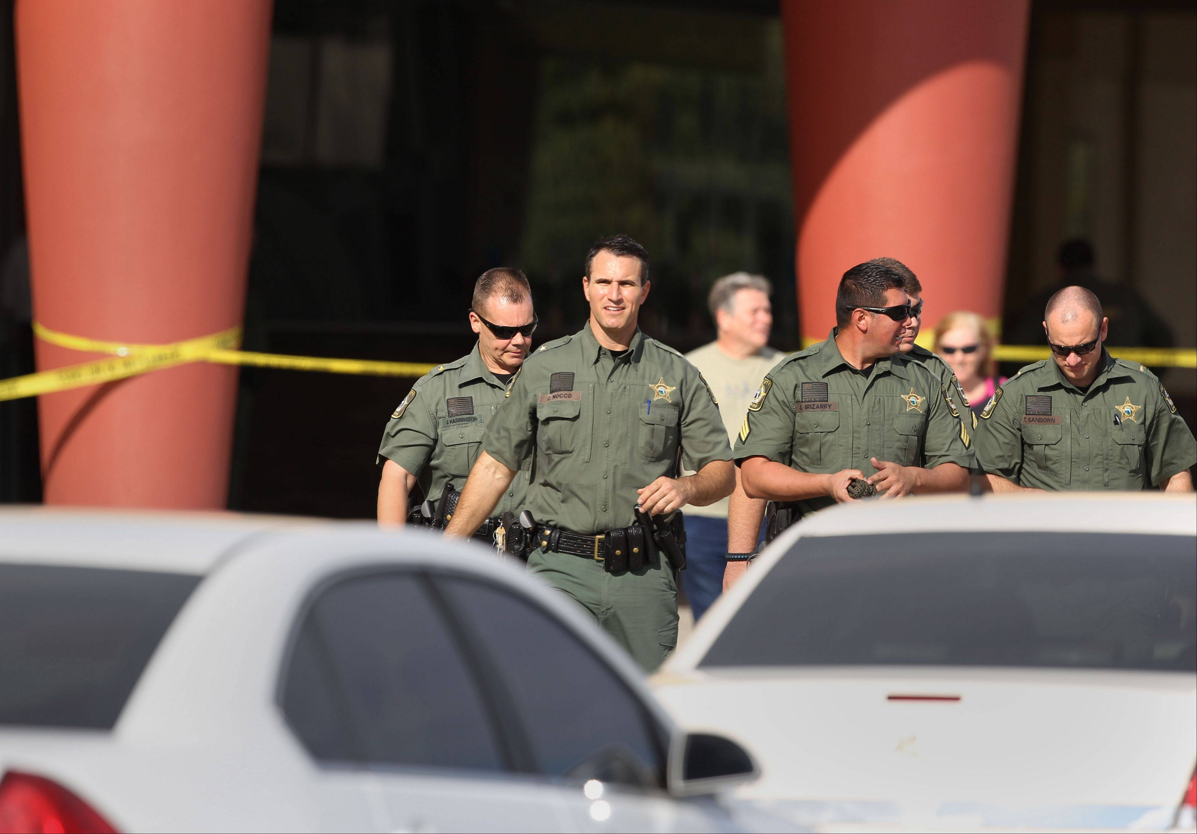 Pasco Sheriff Chris Nocco, front, walks out to update reporters after an argument between patrons over texting sparked a shooting that left one person dead and another injured in a Pasco County movie theater Monday Jan. 13, 2014, sheriff's officials said.