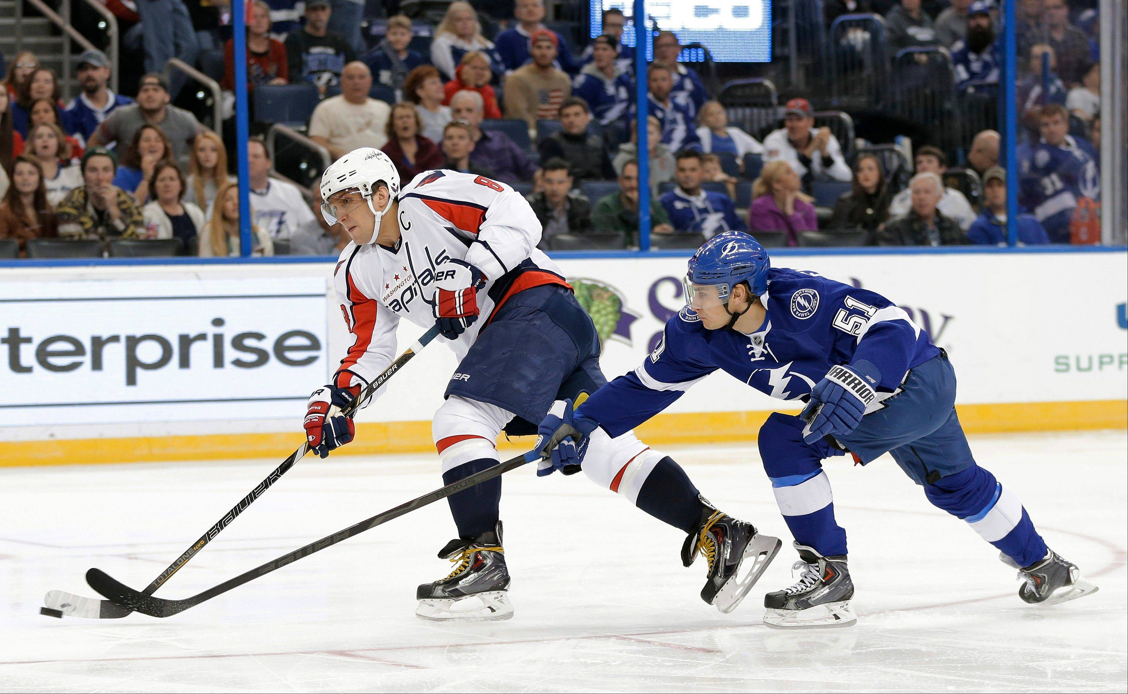 Washington Capitals right wing Alex Ovechkin (8), of Russia, fires the puck on goal after getting past Tampa Bay Lightning center Valtteri Filppula (51), of Finland, during the first period of an NHL hockey game Thursday, Jan. 9, 2014, in Tampa, Fla.