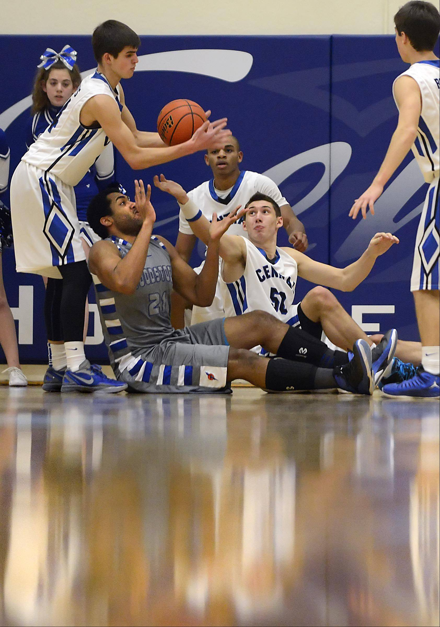 Burlington Central�s Brett Rau grabs the loose ball as teammate Duncan Ozburn and Woodstock�s Damian Stoneking reach from the floor Wednesday in Burlington.