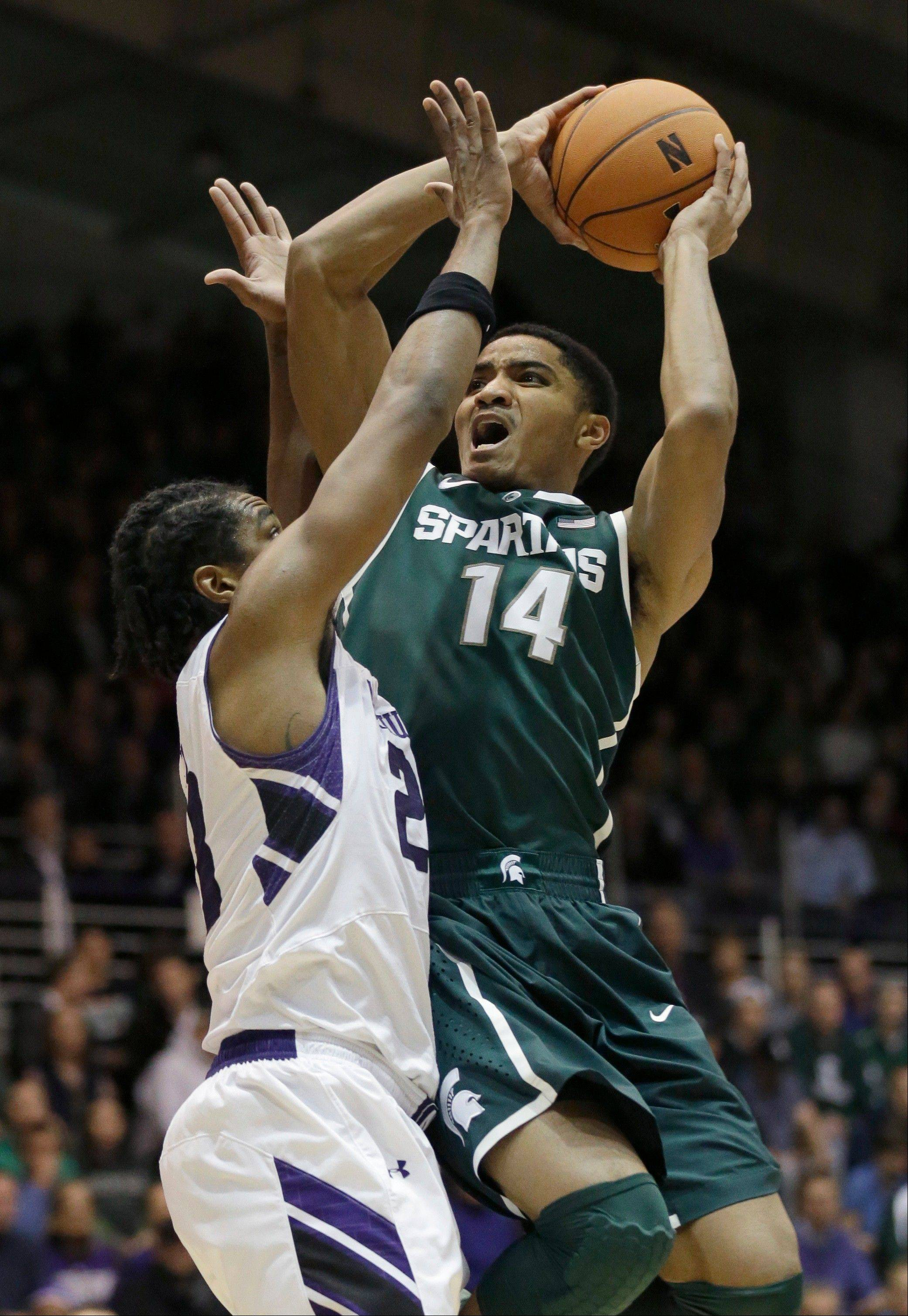Michigan State guard Gary Harris, right, drives to the basket as Northwestern guard JerShon Cobb defends against him during the first half of an NCAA college basketball game Wednesday in Evanston.