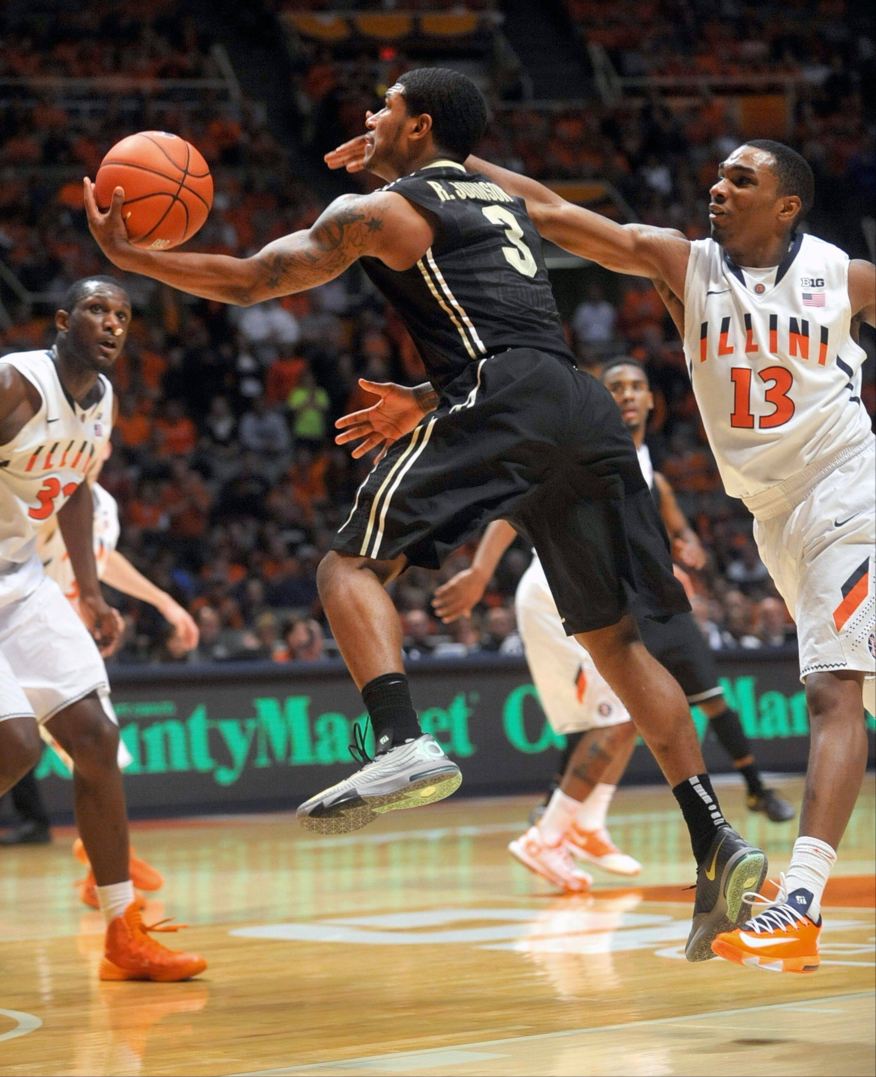 Purdue guard Ronnie Johnson (3) glides past Illinois guard Tracy Abrams (13) during the second half of an NCAA college basketball game Wednesday in Champaign. Purdue won 66-58.