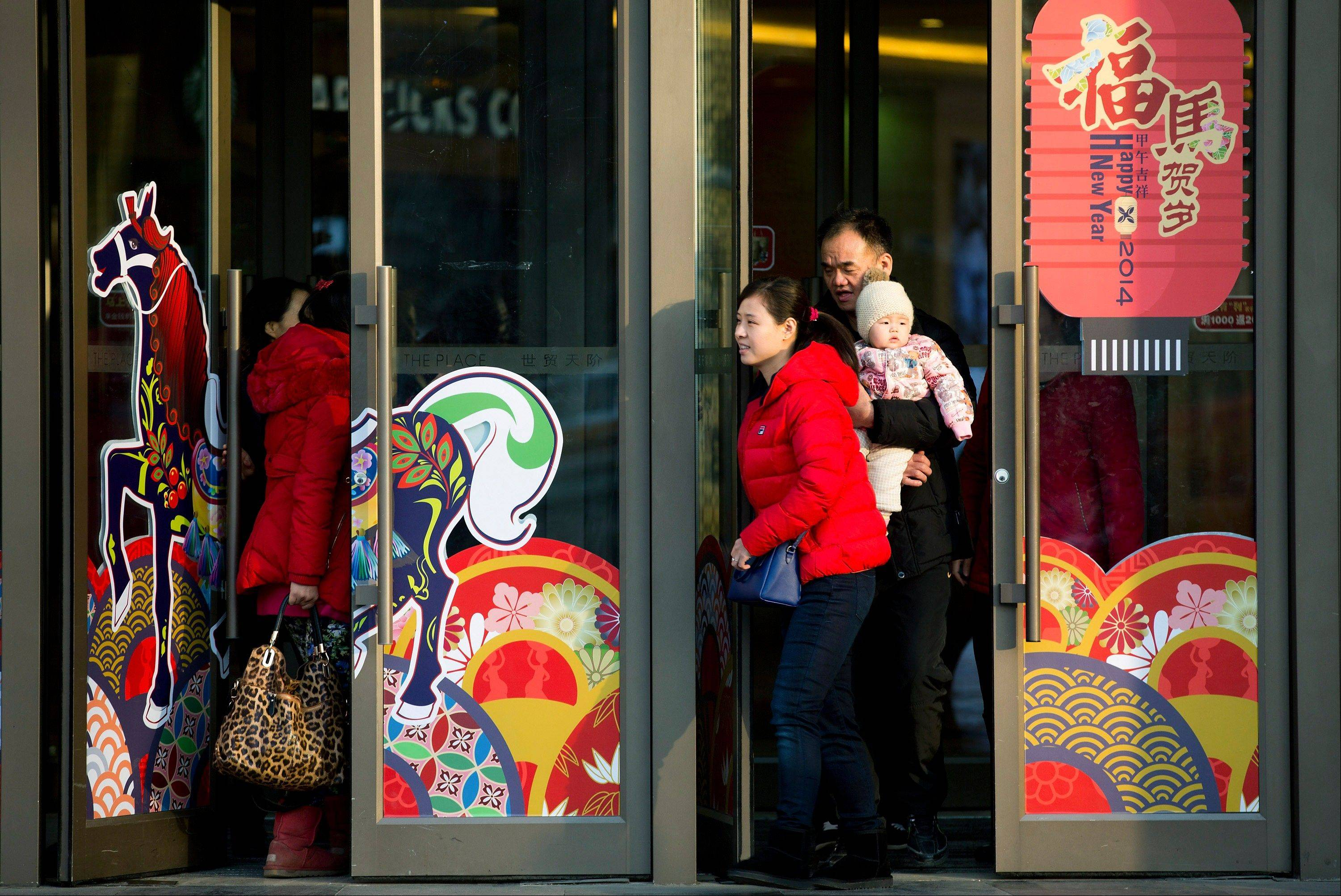 Chinese shoppers walk through entrance doors decorated for the upcoming Chinese Lunar New Year at a shopping mall in Beijing Wednesday. The global economy is slowly picking up steam, led by advanced economies appearing to turn the corner after five years of financial crises and recession and a continued good performance by China, the World Bank said.