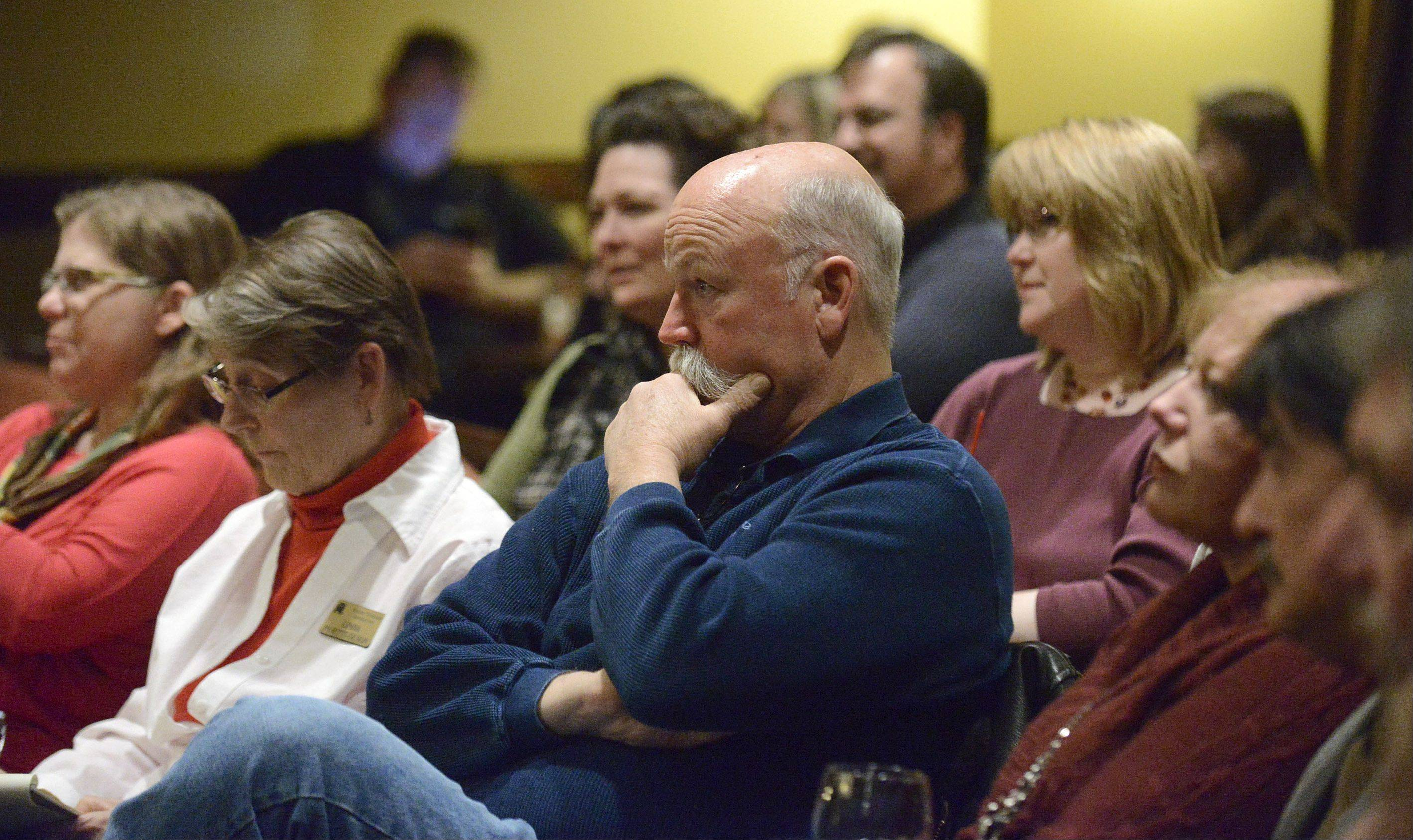 Rick Olson of Montgomery listens to Bill Keck of Sugar Grove and Keith Wheeler of Oswego engage in a debate hosted by the Kane County Young Republicans on Wednesday in Aurora.