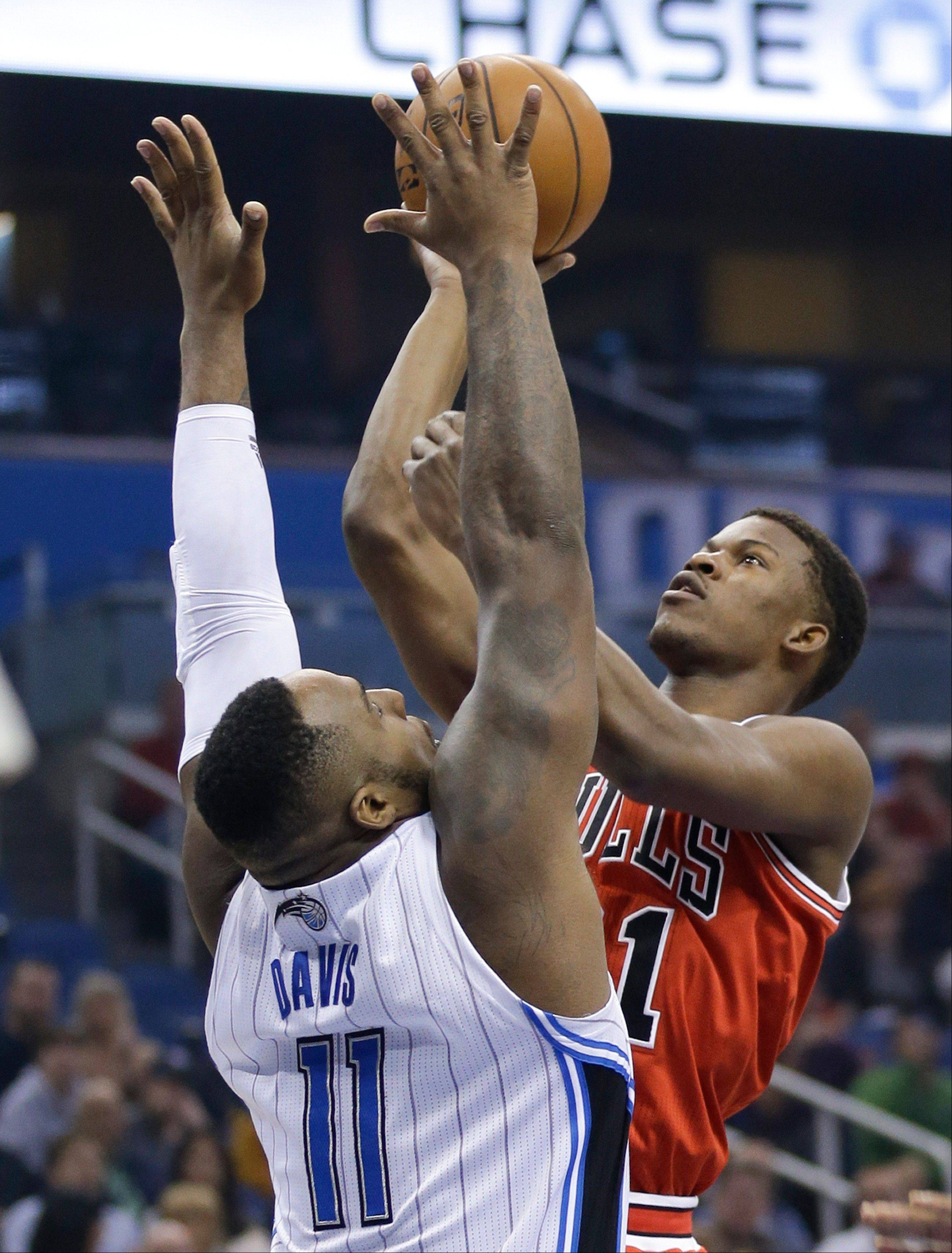 Jimmy Butler, taking a shot over Orlando's Glen Davis on Wednesday night, set at Bulls record by play 60 minutes, 20 seconds in the Bulls' triple-overtime victory over the Magic.