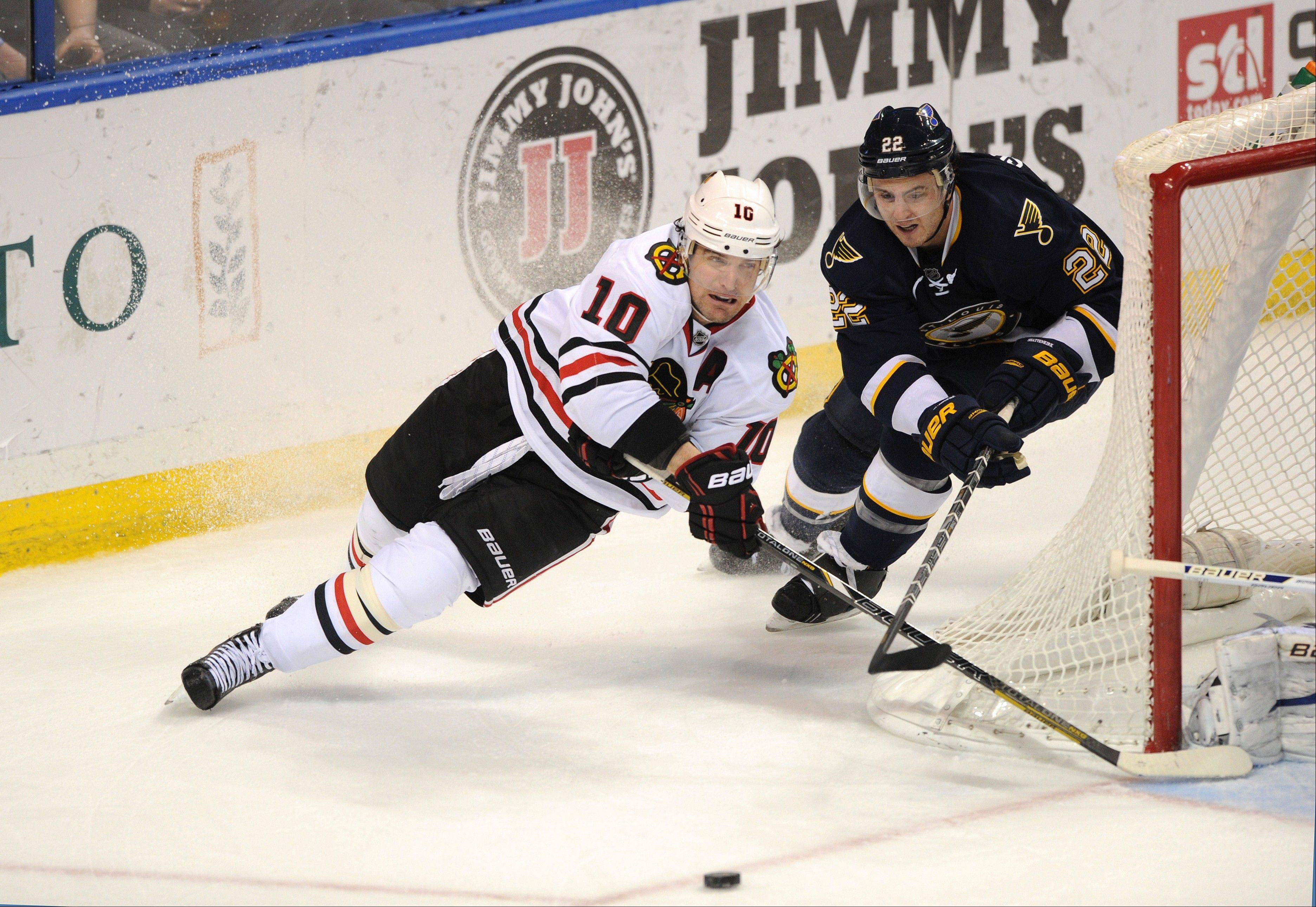 St. Louis Blues' Kevin Shattenkirk (22) and Chicago Blackhawks' Patrick Sharp (10) reach for the puck in an NHL hockey game Saturday, Dec. 28, 2013, in St. Louis.