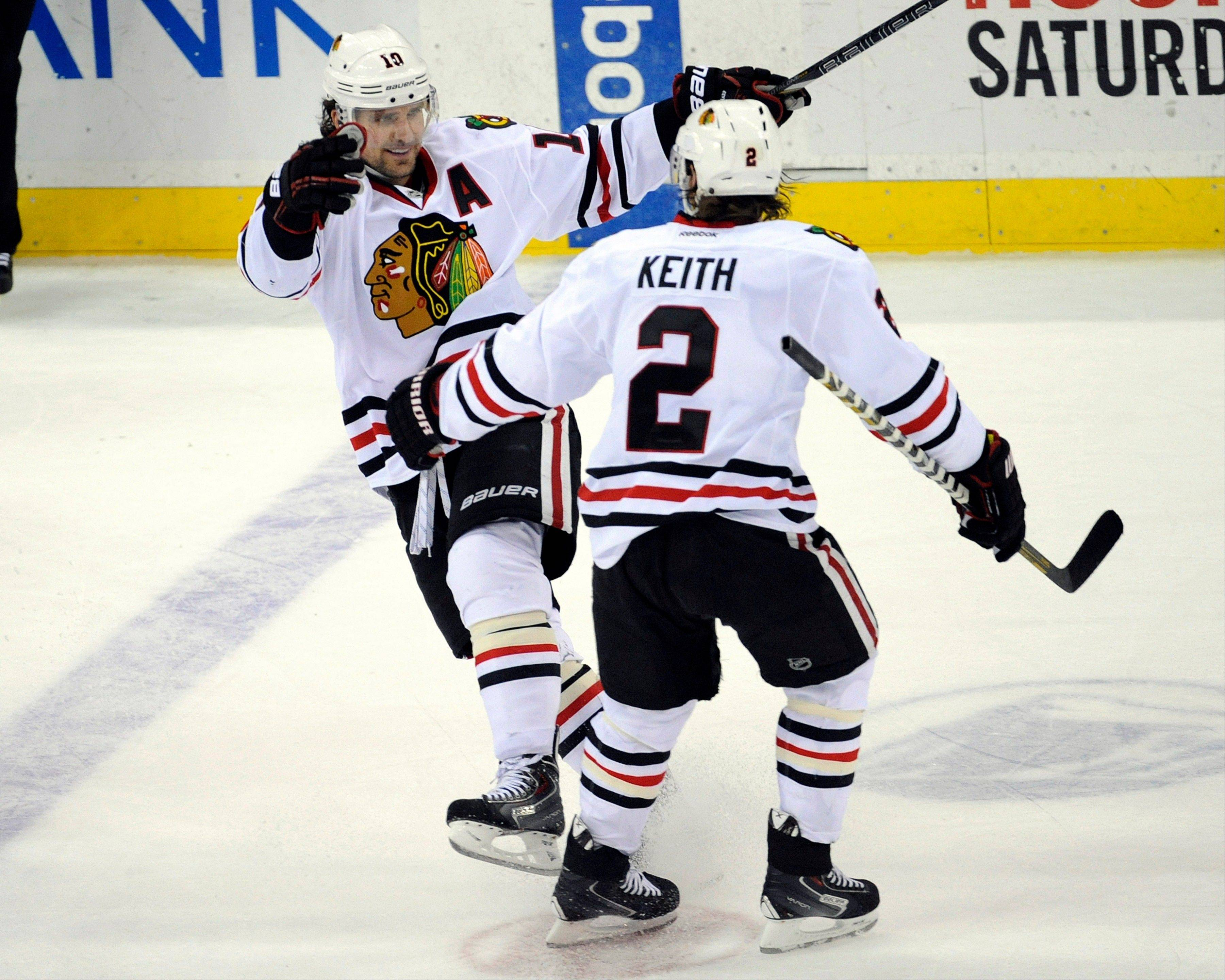 Patrick Sharp celebrates his hat trick with Duncan Keith (2) during the third period of an NHL hockey game against the New Jersey Devils, Friday, Jan. 3, 2014, in Newark, N.J. The Blackhawks won 5-3.