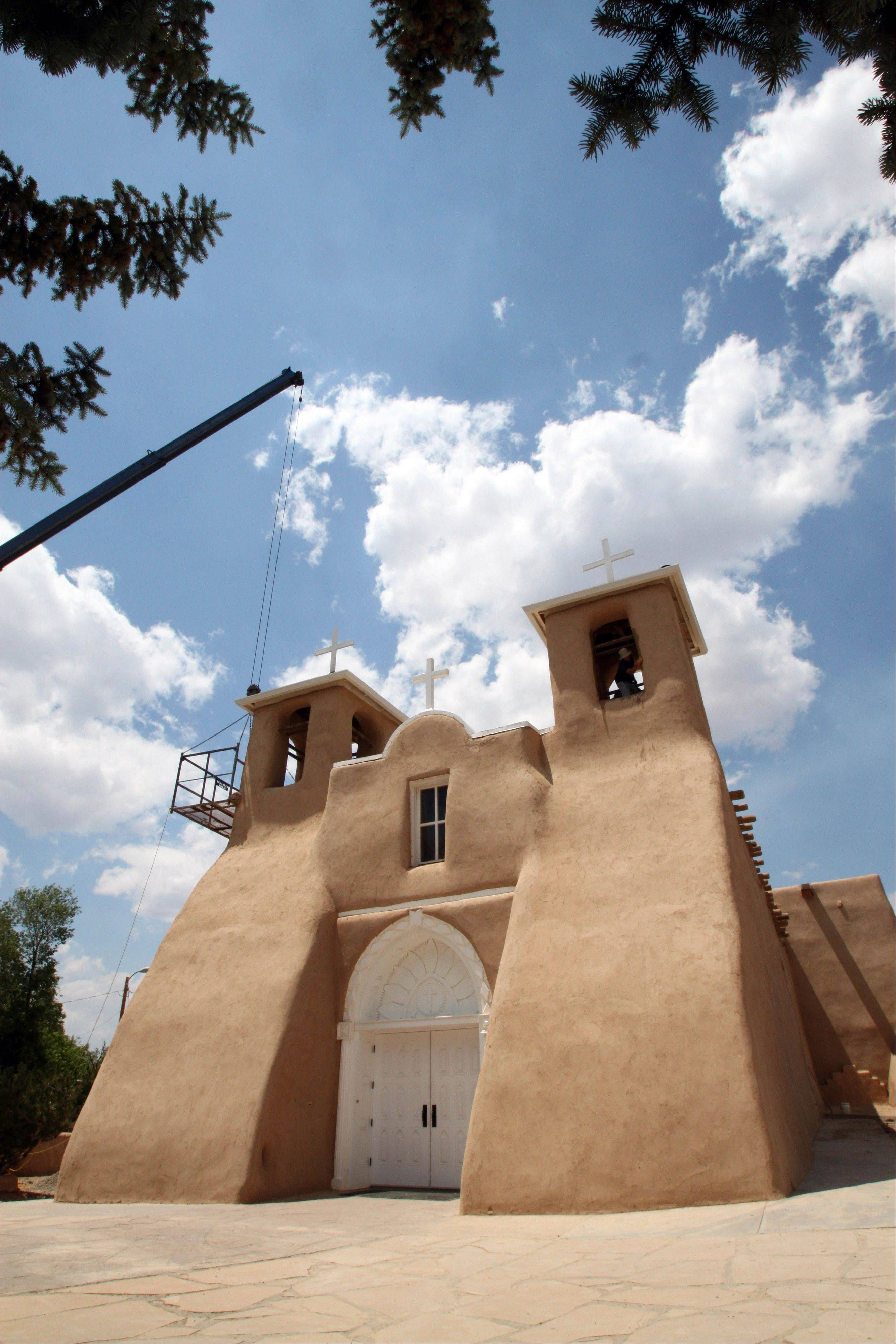 Workers apply mud to the San Francisco de Asis Church in Ranchos de Taos, N.M., as part of an annual ritual that has been done for nearly 200 years. The historic church was made famous by the paintings of Georgia O�Keeffe and the photographs of Ansel Adams and Paul Strand.