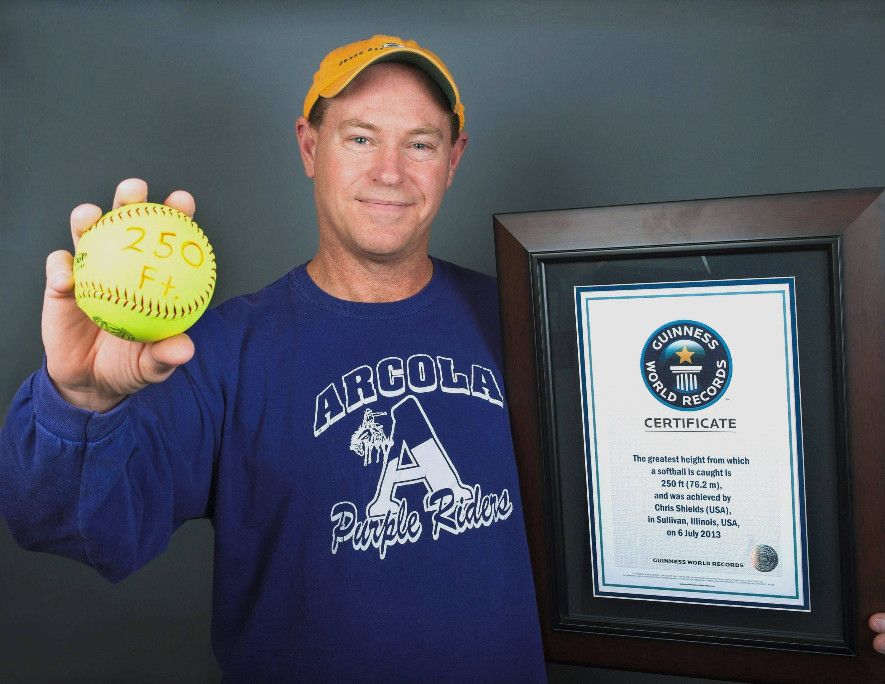 Chris Shields, 53, of Champaign poses with a plaque and softball after he set the Guinness World Records Book mark for catching a softball from the greatest height.