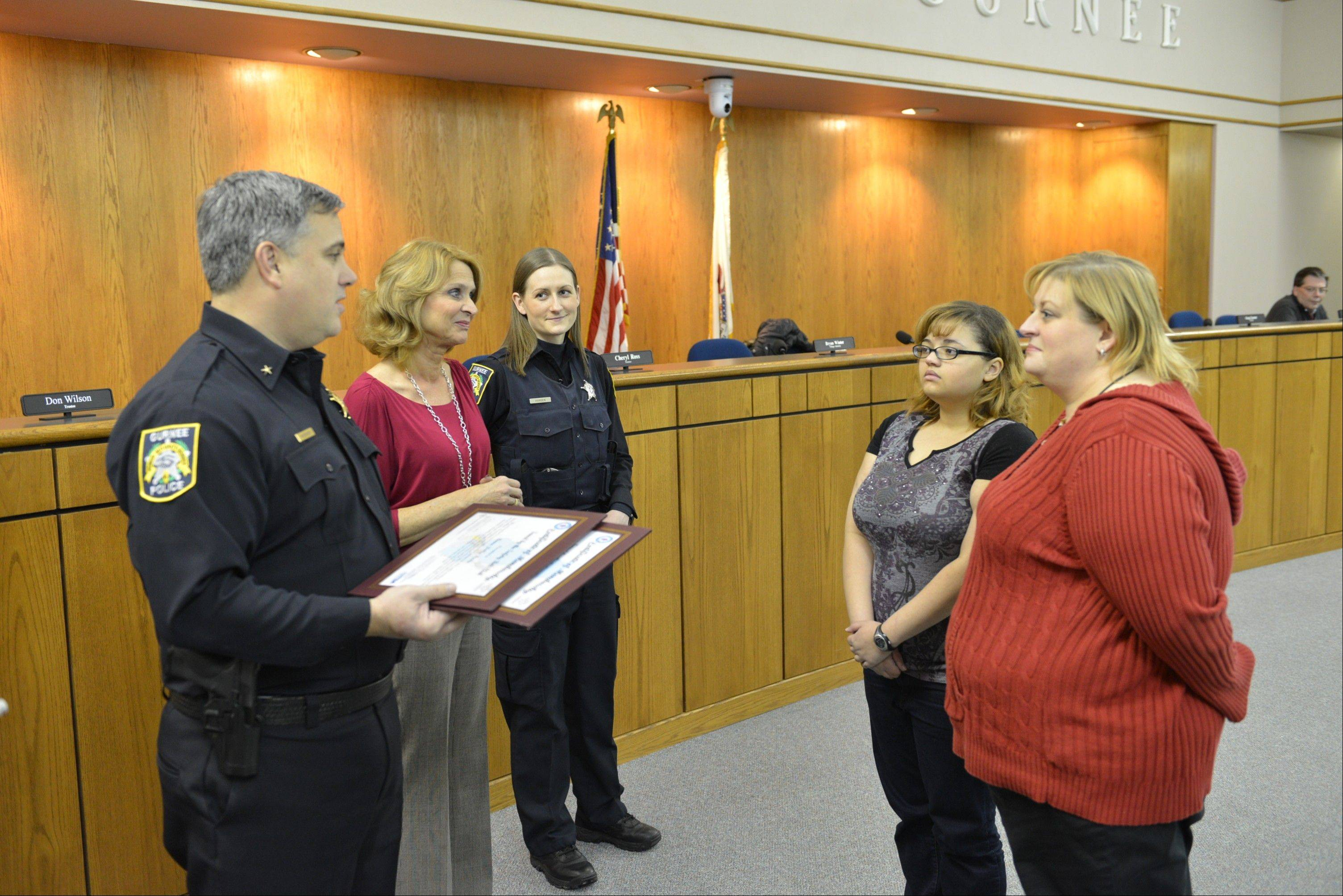 Gurnee Police Chief Kevin Woodside, left, and Mayor Kristina Kovarik were accompanied by officer Kelly Hansen at the village hall when they presented Saved by the Safety Belt honors to Anna Della Posta, far right, and her daughter, Jasmine Washington.