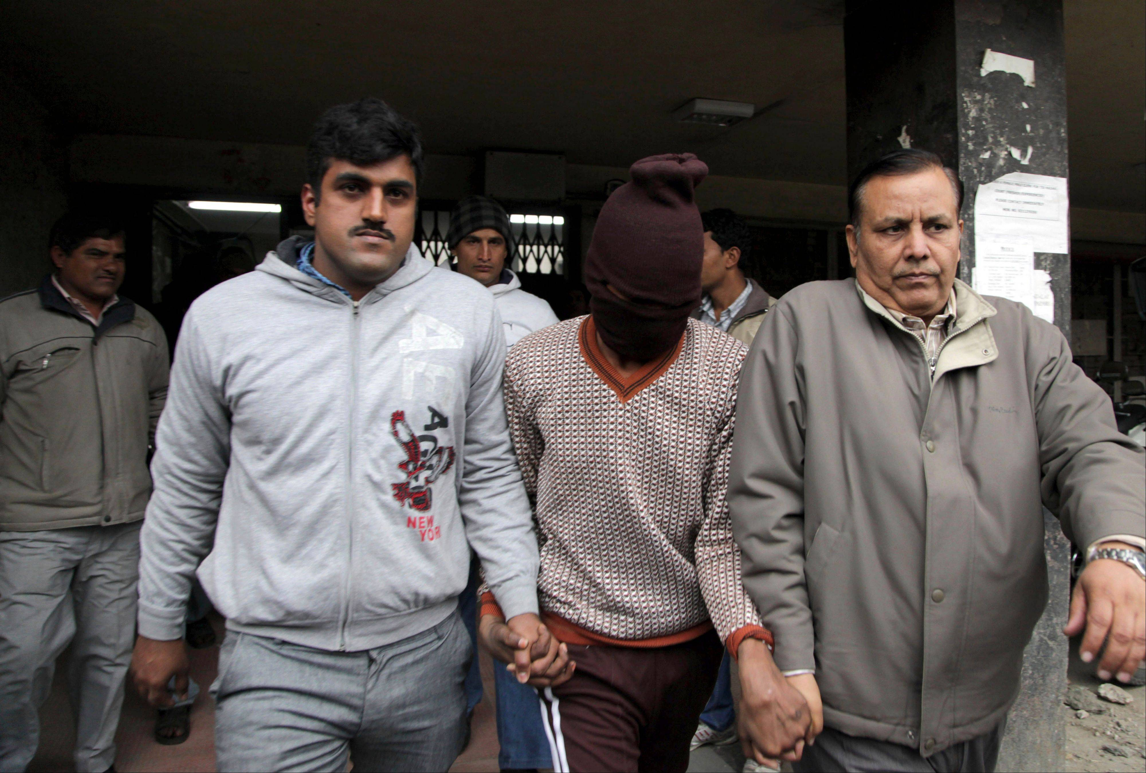 Police officials escort an accused in the gang rape of a 51-year-old Danish tourist as they walk out of a court in New Delhi, India, Thursday, Jan. 16, 2014.