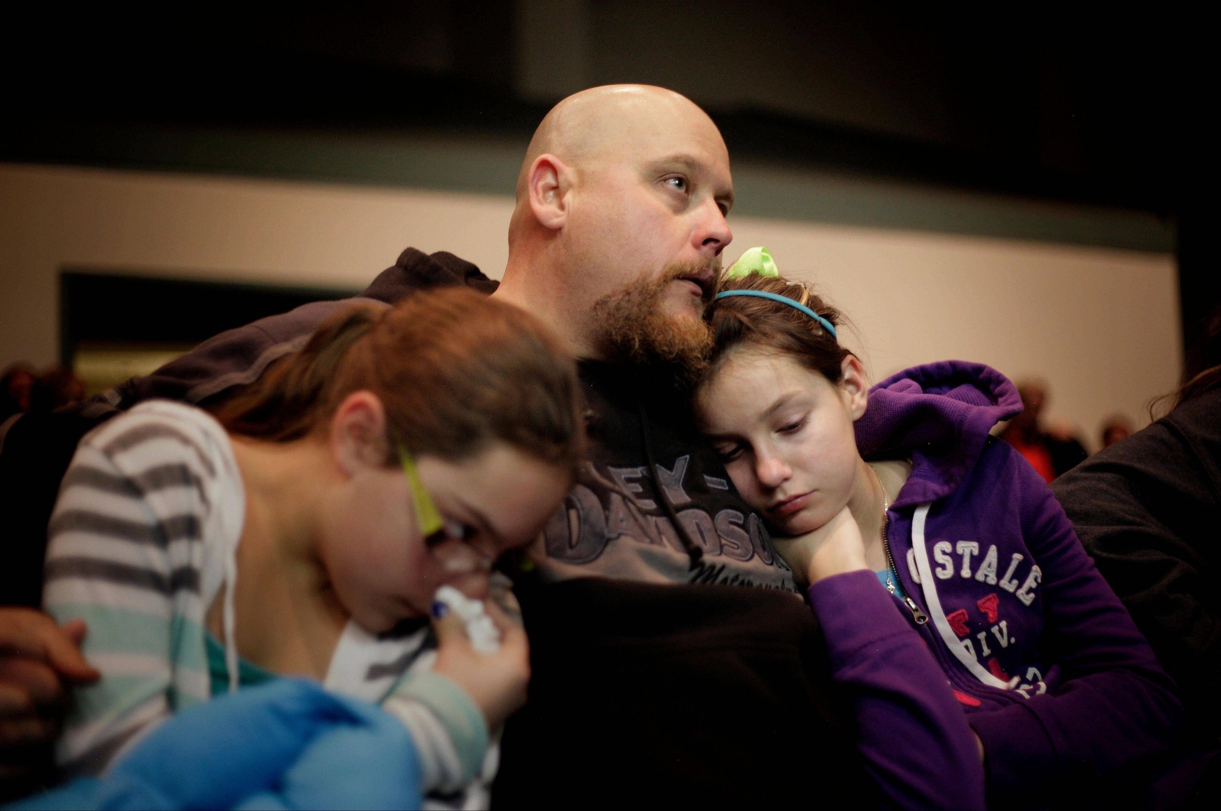 Troy Tucker, center of Roswell, N.M., holds his daughters Emily Tucker, left age 10, and Hannah Tucker, right age 12, during a community prayer vigil for the victims of the Berrendo Middle School shooting in Roswell, N.M., Tuesday Jan. 14, 2014.