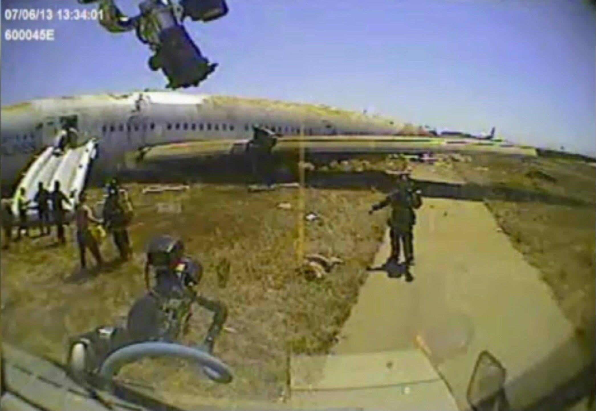 This image from the video camera of a San Francisco fire battalion firetruck at the scene of the crash of Asiana Flight 214 on July 6, 2013, shows a firefighter directing the firetruck around the body of passenger Ye Meng Yuan at San Francisco International Airport in San Francisco.