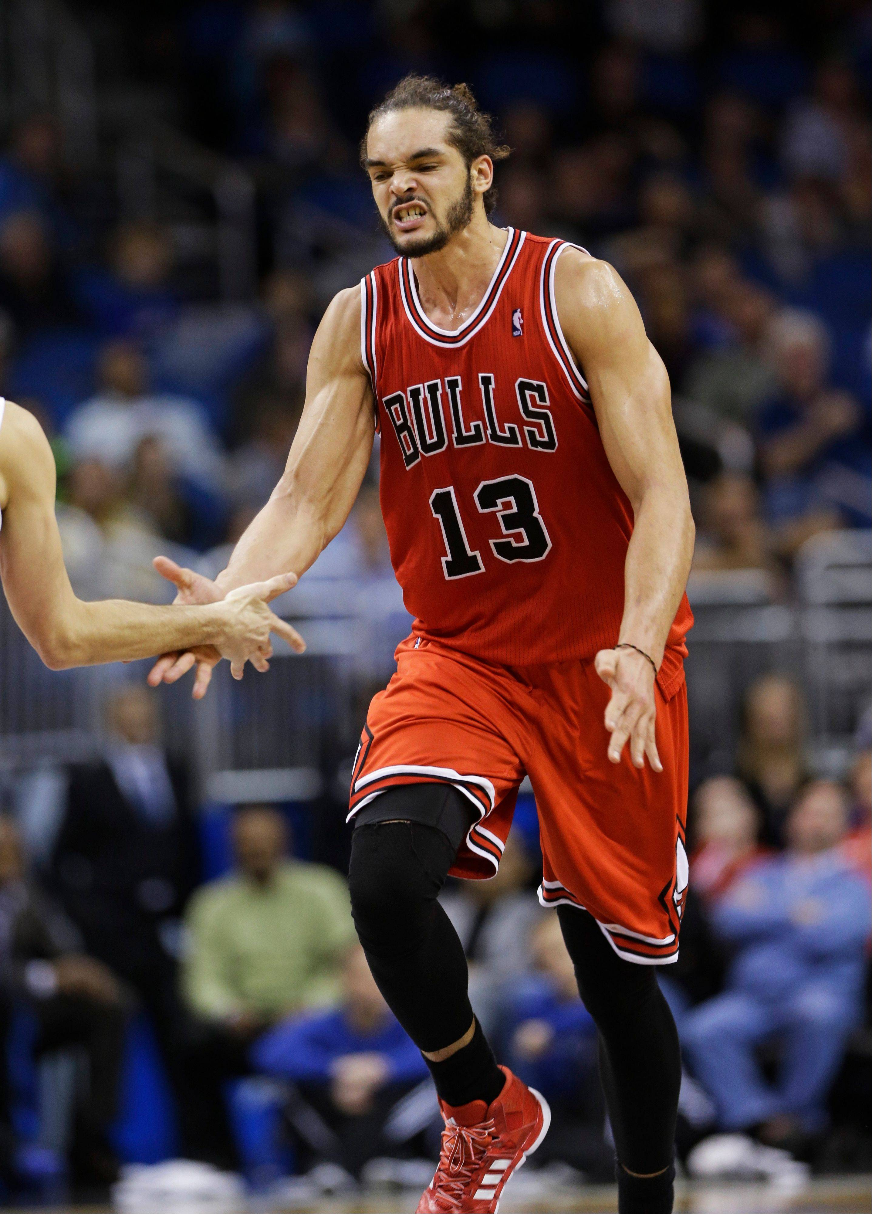 Chicago Bulls' Joakim Noah (13) slaps hands with teammate Kirk Hinrich after sinking a shot during the second half of an NBA basketball game against the Orlando Magic in Orlando, Fla., Wednesday, Jan. 15, 2014. Chicago won in triple overtime, 128-125. (AP Photo/John Raoux)