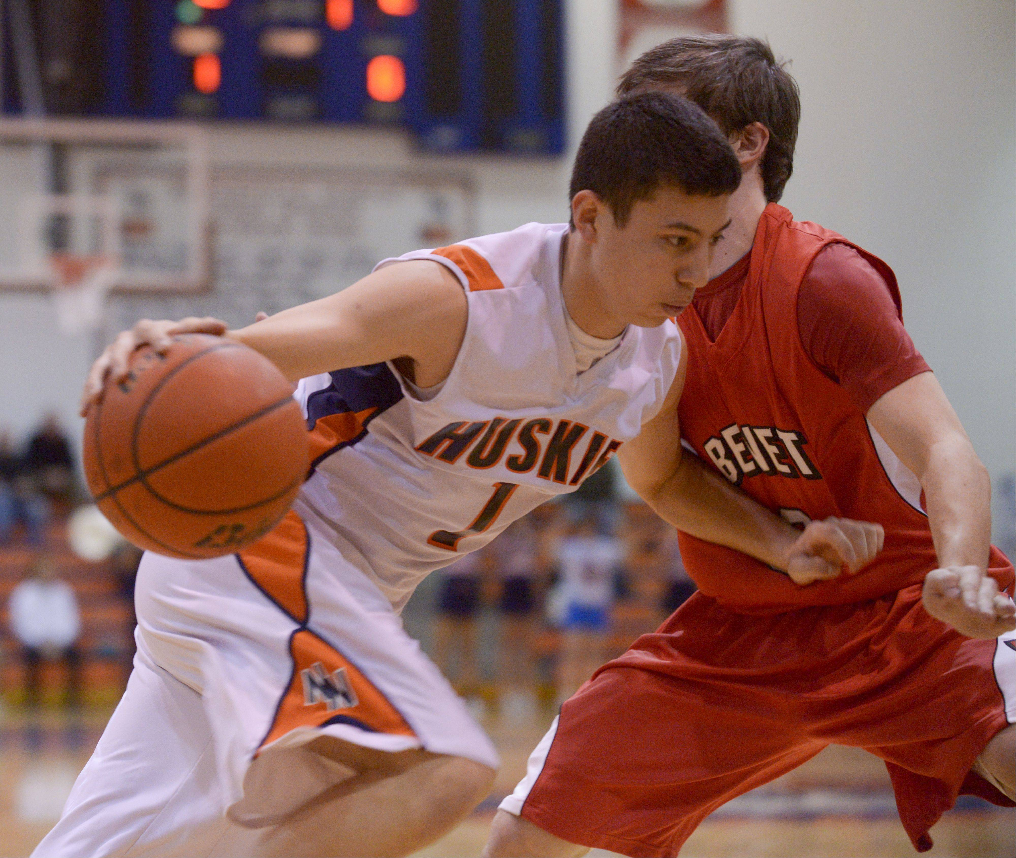 Naperville North�s Jayson Winick drives around Benet�s Collin Pellettieri during in boys basketball in Naperville Sunday.
