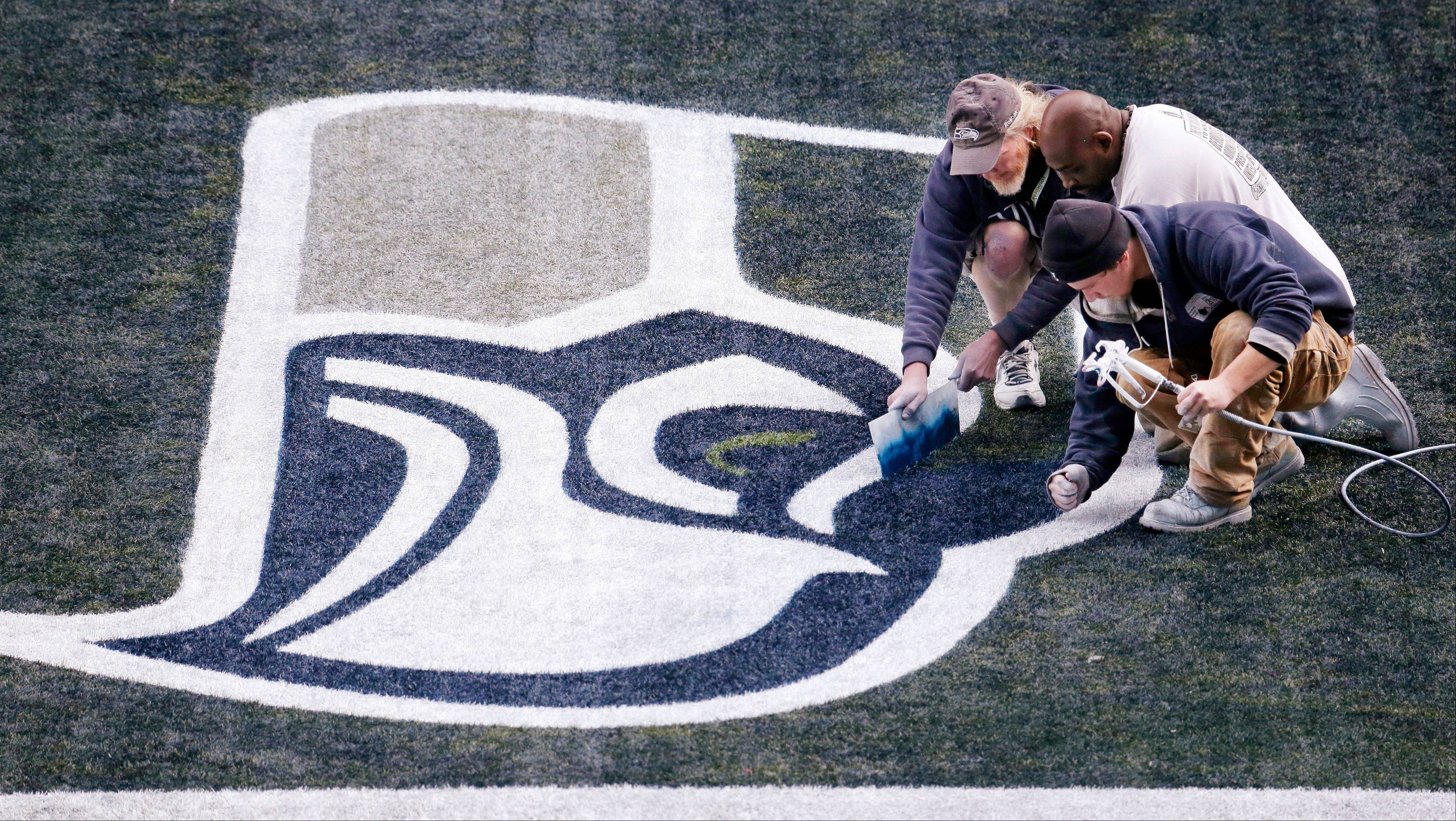 Painters put the finishing touches on a Seattle Seahawks' logo on the turf at CenturyLink Field in preparation for the NFL football NFC championship game in Seattle, Wednesday, Jan. 15, 2014. The Seahawks play the San Francisco 49ers on Sunday. (AP Photo/Elaine Thompson)