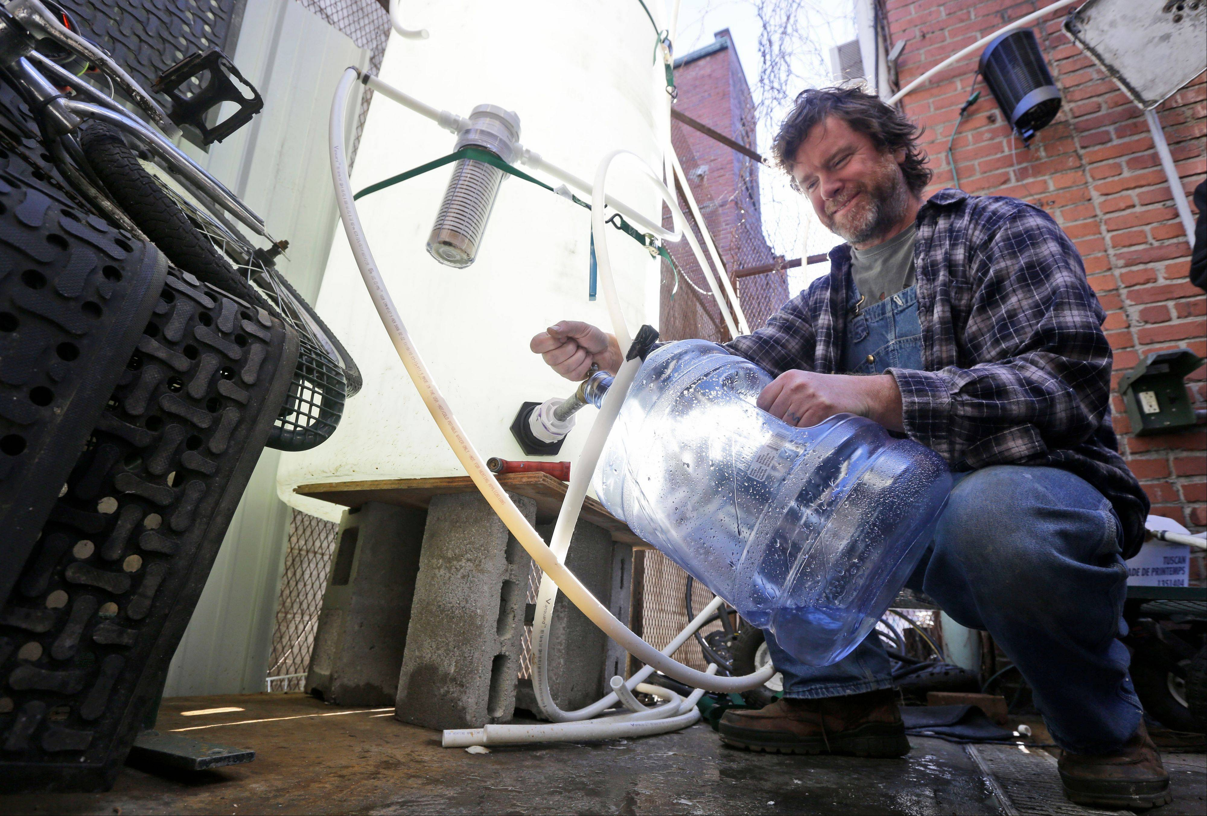 Jonathan Steele, owner of Bluegrass Kitchen, fills a jug with cleaning water in the back of his restaurant in Charleston, W.Va., Tuesday, Jan. 14, 2014. Steele installed a large tank in the back of his restaurant and was able to open using bottled water on Sunday.