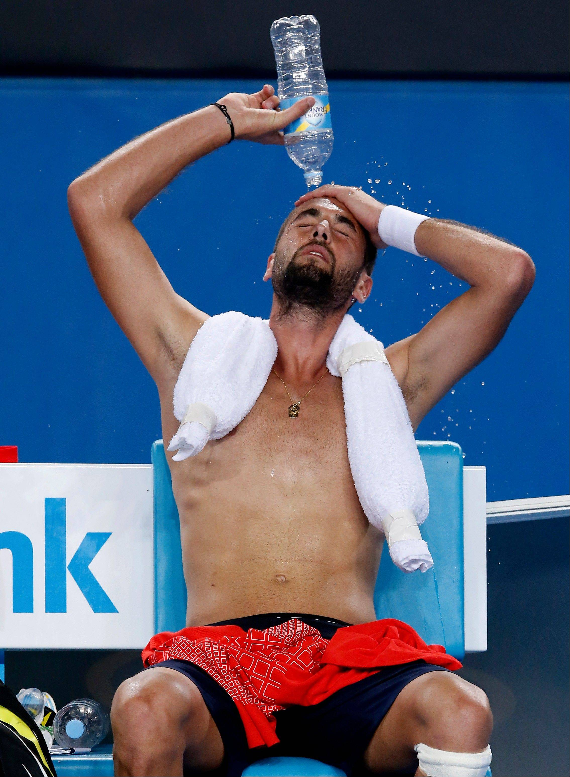 Benoit Paire of France pours water over his face during a break in his second round match against Nick Kyrgios of Australia at the Australian Open tennis championship in Melbourne, Australia, Thursday, Jan. 16, 2014.